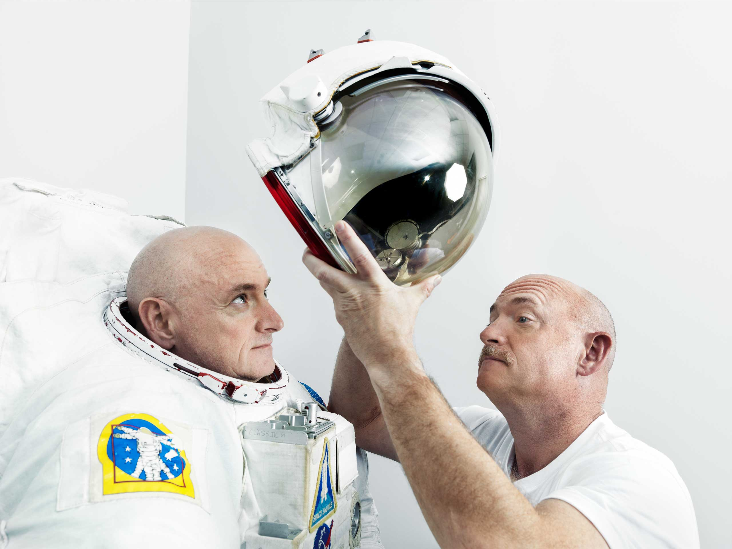 Mark Kelly places a helmet on his twin brother, Scott Kelly, at Johnson Space Center in Houston.