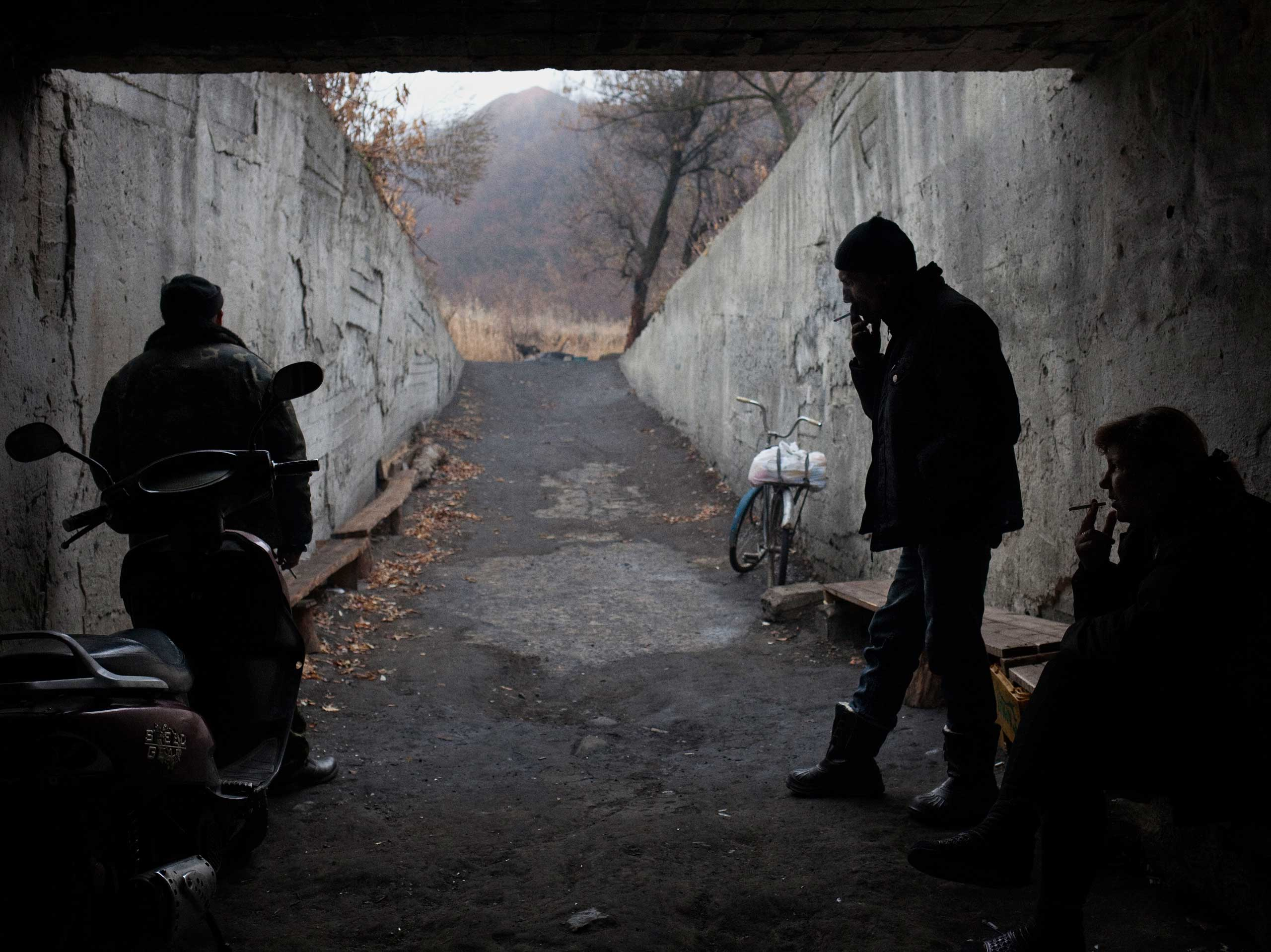 A woman and two men smoke cigarettes outside a World War II-era bomb shelter near the Trudovsky coal mine. About 40 to 50 people live in the shelter, the majority of whom are miner families. Petrovskyi district, Donetsk, Ukraine. Nov. 19, 2014.