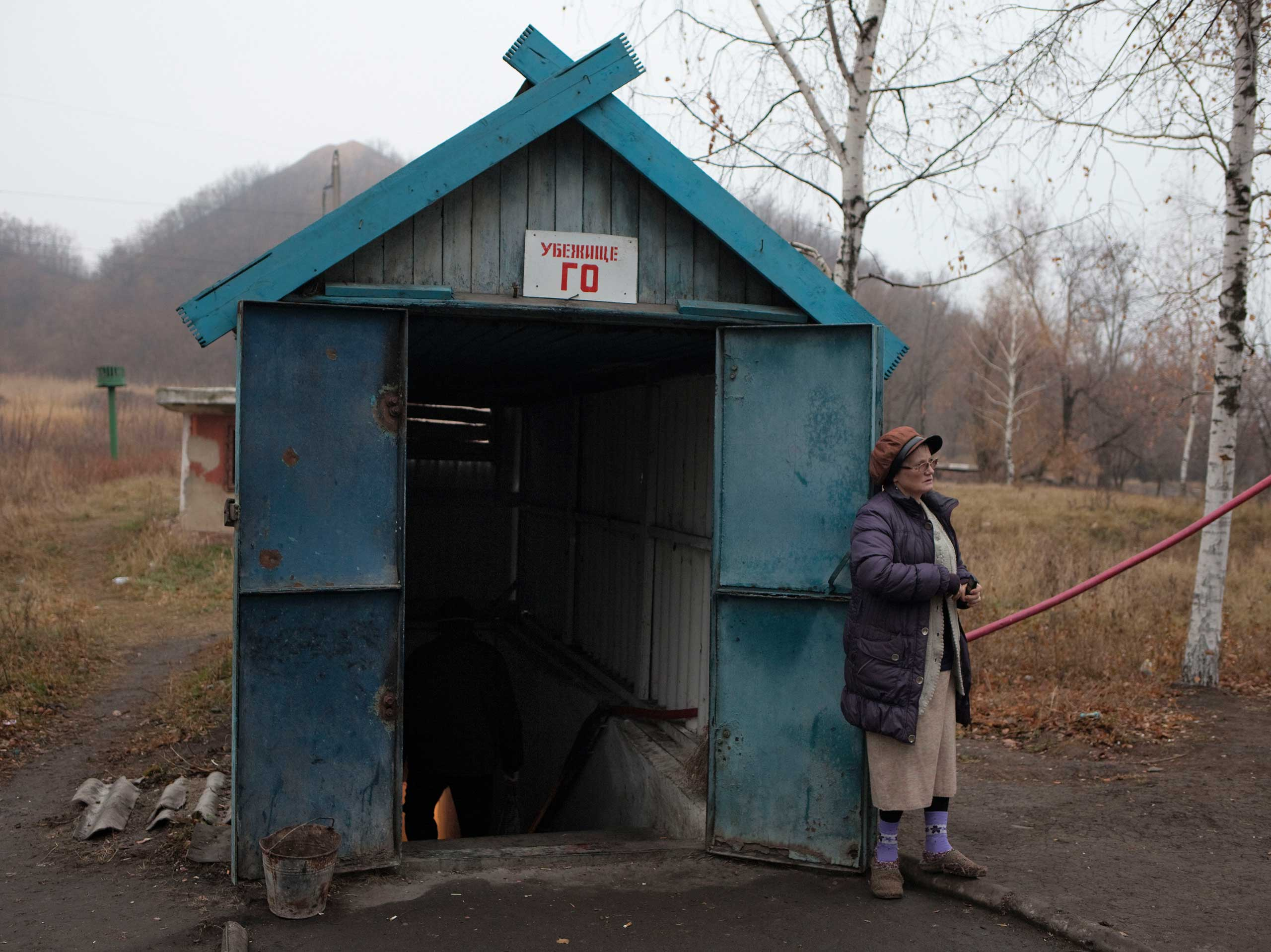 A woman outside an entrance to a bomb shelter near a coal mine. She was making a phone call and smoking a cigarette. Petrovskyi district, Donetsk, Ukraine. Nov. 19, 2014.