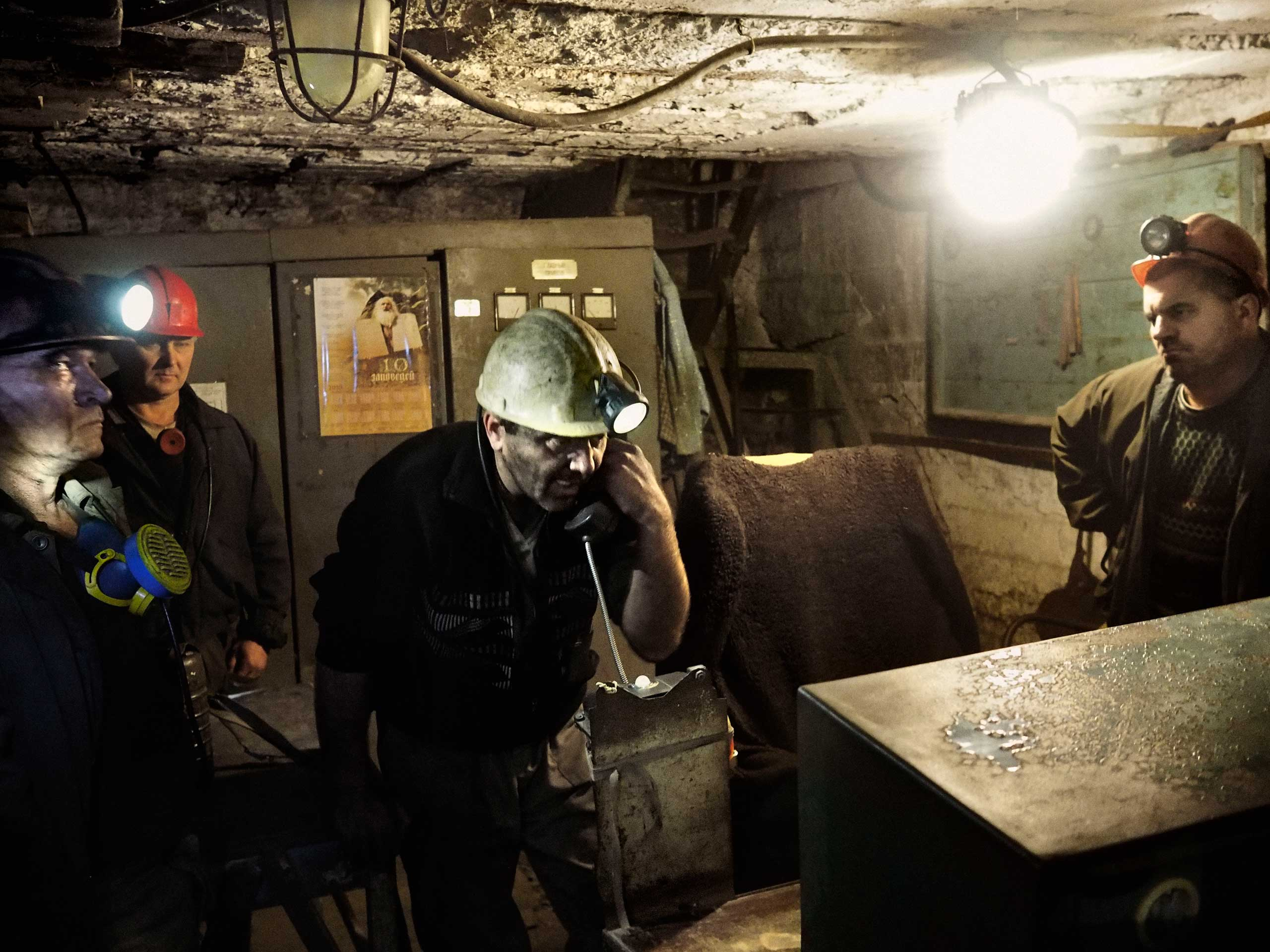Working by the light of an emergency generator, the mine's deputy director begins evacuation preparations after being told that a Ukrainian army shell had damaged the mine's power supply and ventilation system. Petrovskyi district, Donetsk, Ukraine. Nov. 22, 2014.