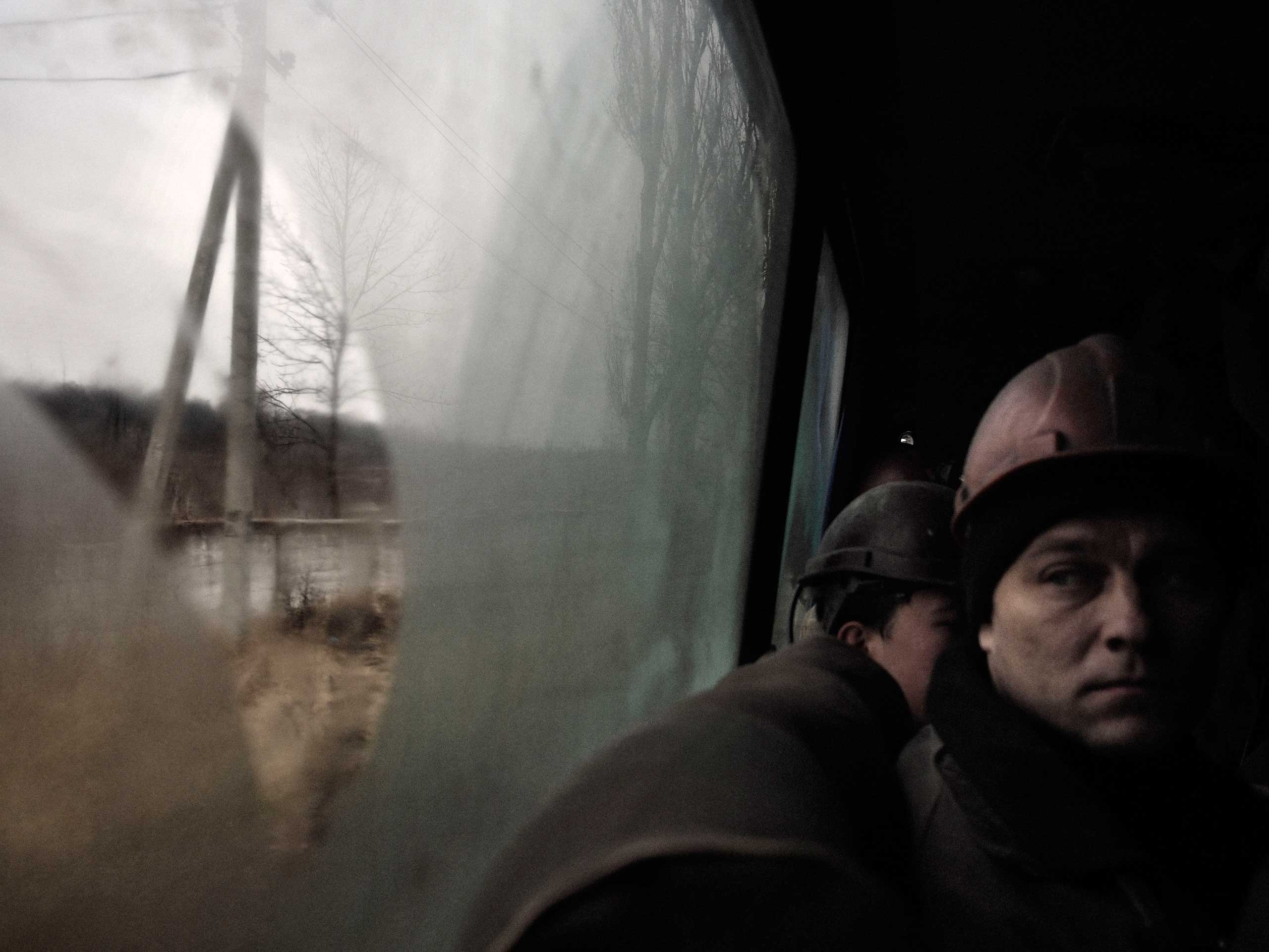 A miner peers out of the bus, seconds after a shell landed 10 meters away, while traveling to the entrance to the mine's deepest shaft. Petrovskyi district, Donetsk, Ukraine. Nov. 24, 2014.