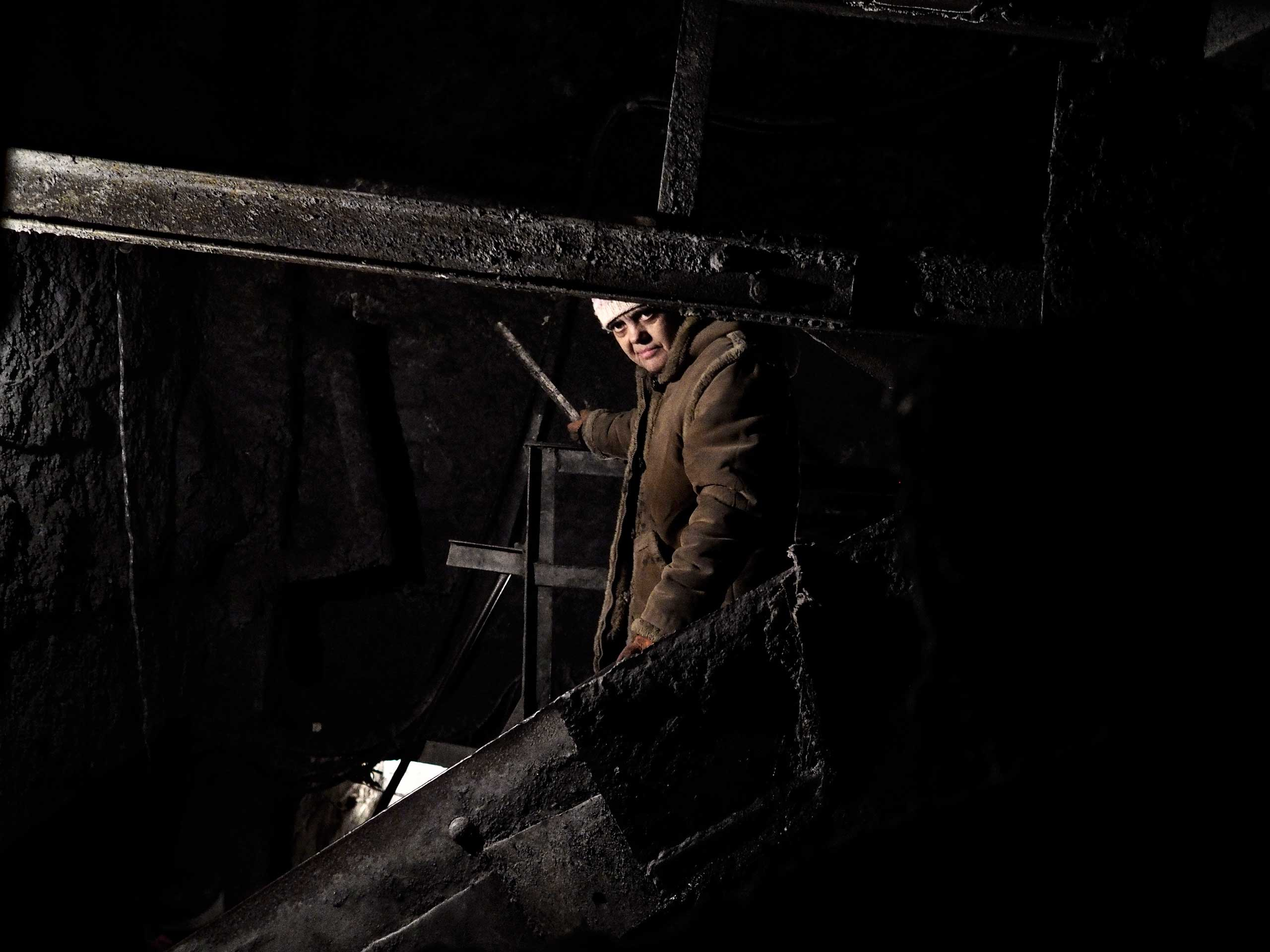 A woman working on the coal conveyer belt in the storage area of the mine complex. Petrovskyi district, Donetsk, Ukraine. Nov. 24, 2014.