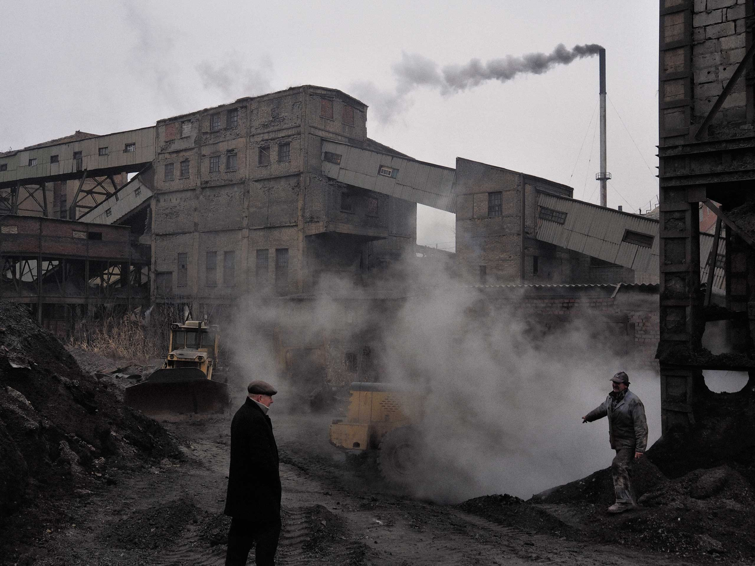 A miner gestures to a supervisor at a storage area for coal situated at the back of the Chelyuskintsev mine complex. Petrovskyi district, Donetsk, Ukraine. Nov. 24, 2014.