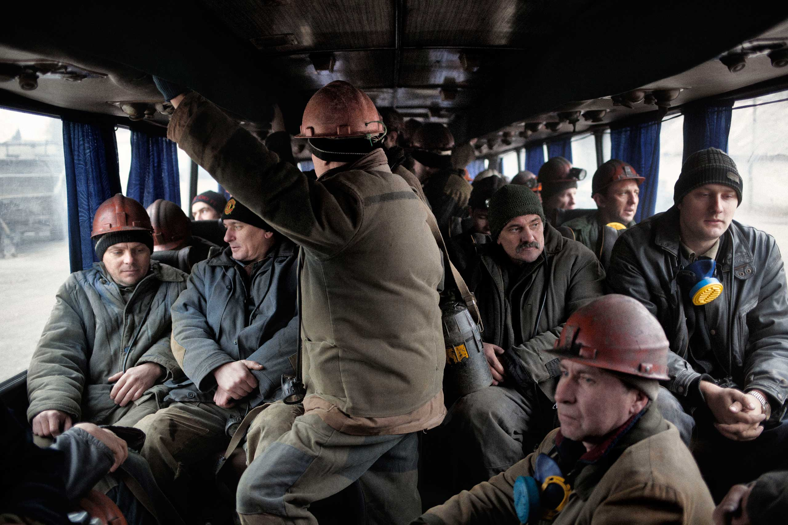 Miners on a bus going to the deepest shaft of the Chelyuskintsev coal mine, 8 kilometers away from the main complex. A shell landed 10 meters from the bus on the way, but they continued to the entrance of the shaft. Upon arrival, they learned that the power had not yet been restored after the shelling two days earlier. Petrovskyi district, Donetsk, Ukraine. Nov. 24, 2014.
