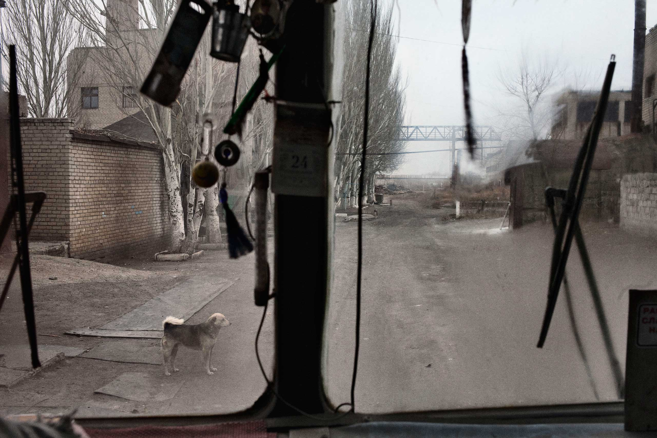 A view from the bus as it approaches the entrance to the mine's deepest shaft. On the left is the shed that was hit by a shell two days earlier. Petrovskyi district, Donetsk, Ukraine. Nov. 24, 2014.