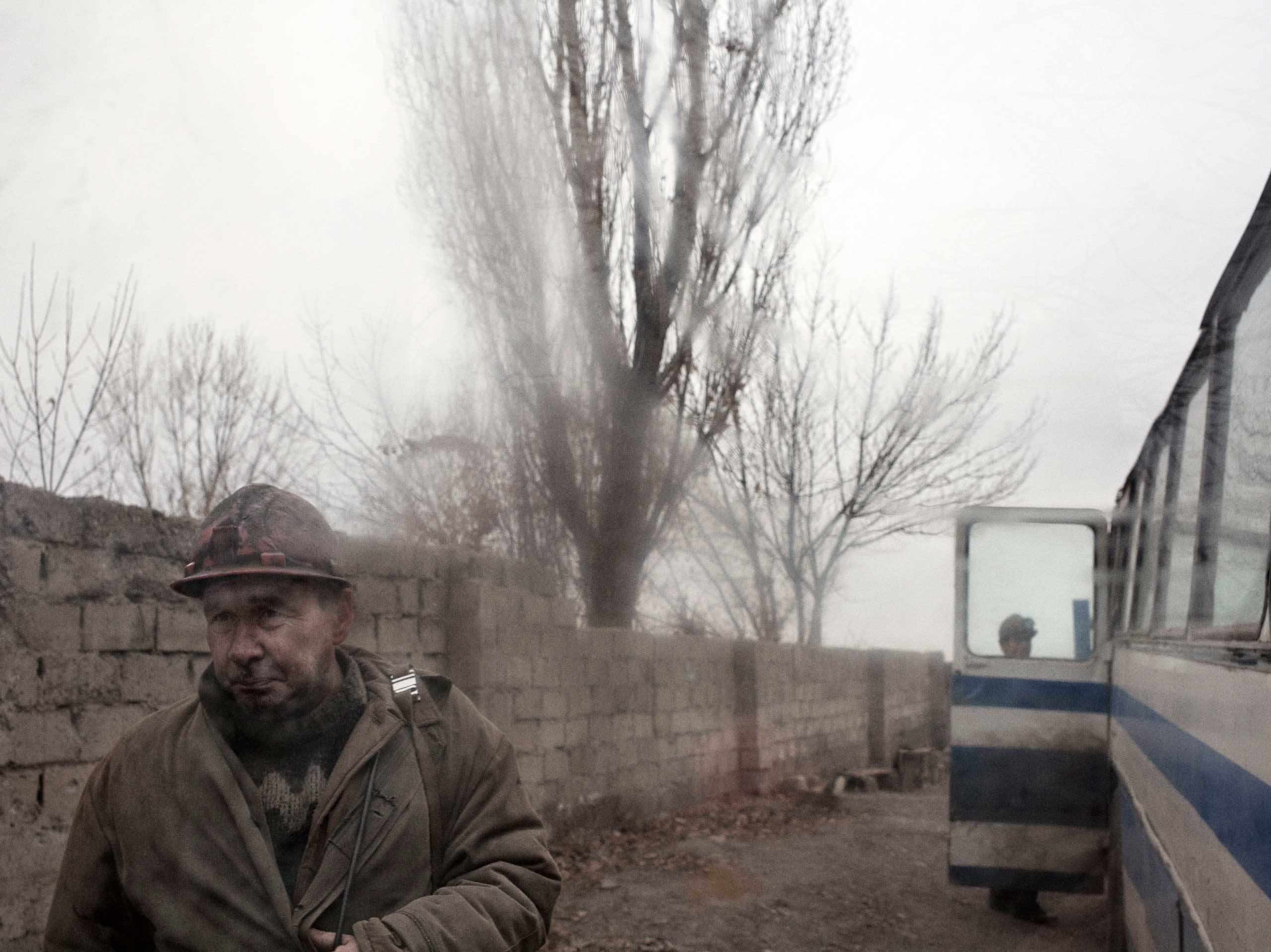A miner outside the bus when it arrived to the deepest shaft of the Chelyuskintsev coal mine, minutes before being told the power had not been restored. Petrovskyi district, Donetsk, Ukraine. Nov. 24, 2014.