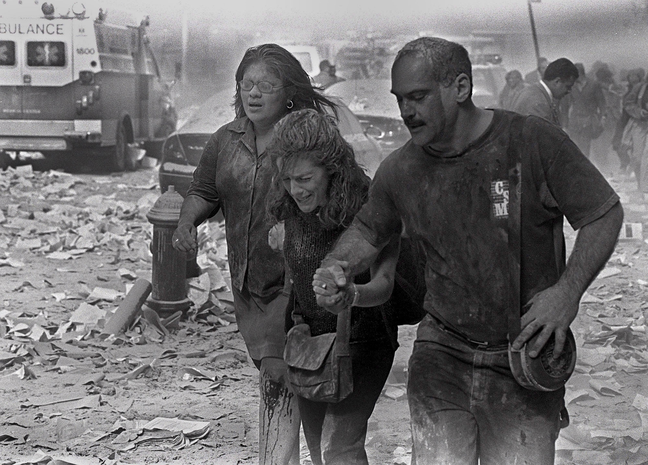 Julie McDermott, center, walks with other victims as they make their way amid debris near the World Trade Center in New York City on Sept. 11, 2001.