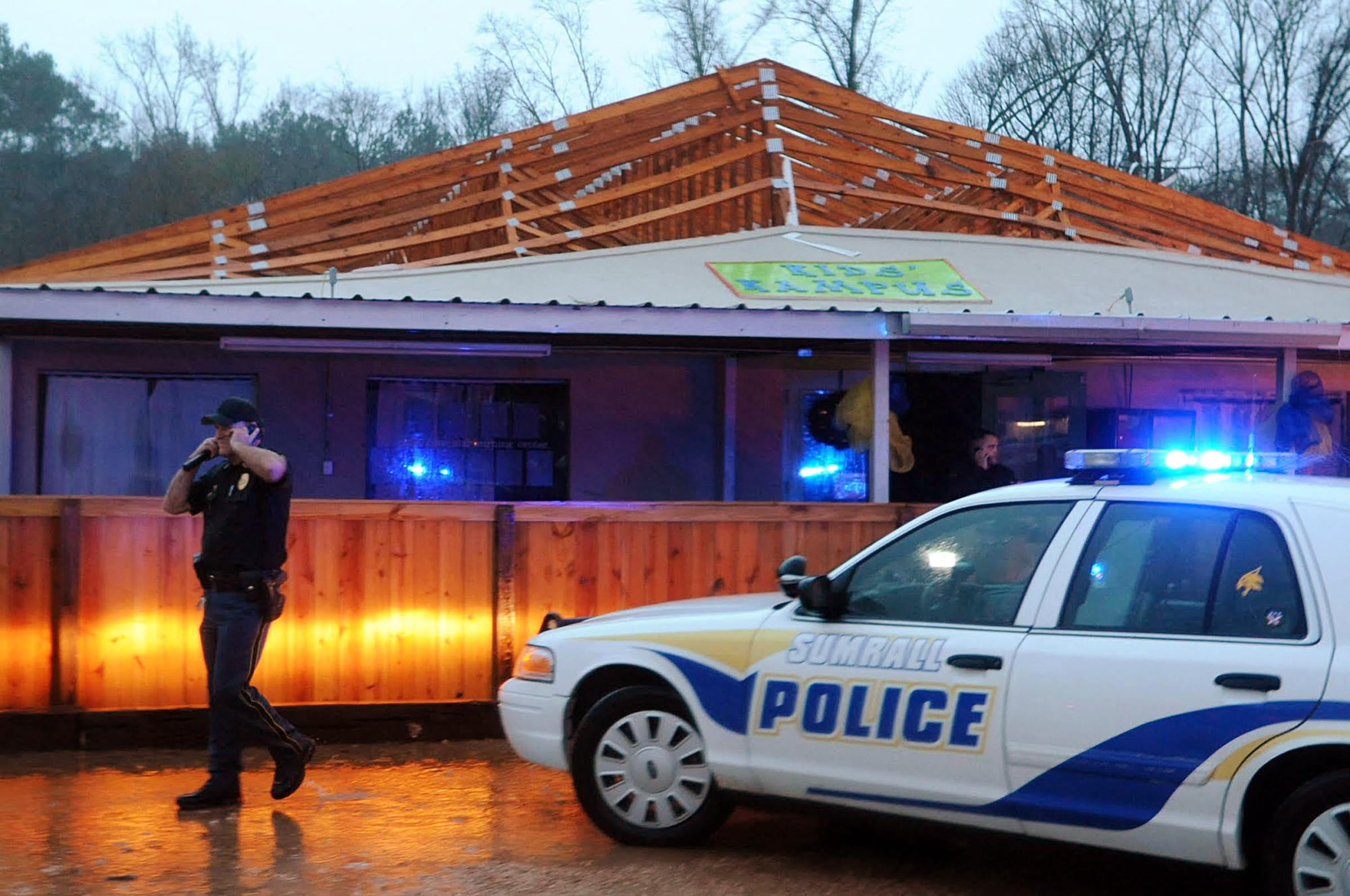Police inspect Kids' Kampus, a day-care facility after a tornado ripped the roof off of the building in Sumrall, Miss., on Dec. 23, 2014