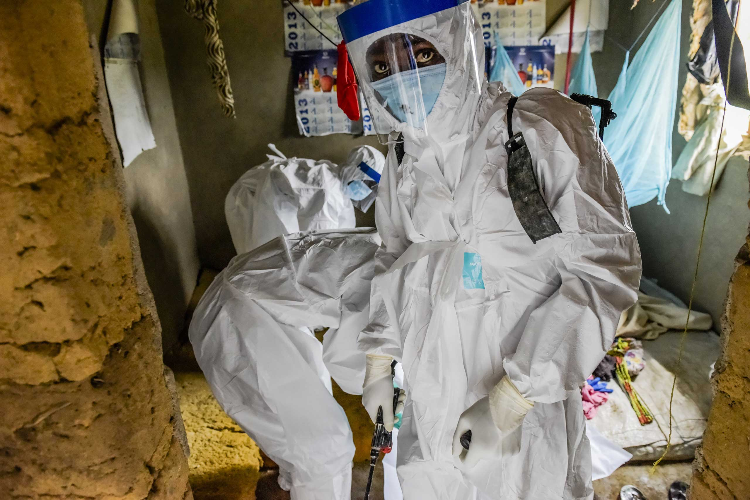 A burial team extracts the body of Isatu Sesay, 16, an Ebola victim, from her home in Kissi Town, Sierra Leone, Nov. 22, 2014.