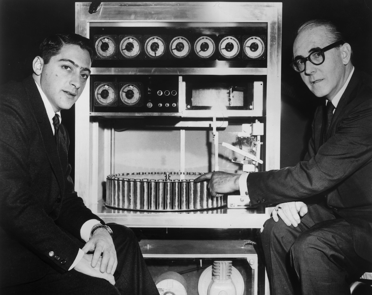 American film producer Mike Todd Jr (left) sits with Swiss inventor Hans Laube, who points to his 'Smell-O-Vision' machine, in 1959