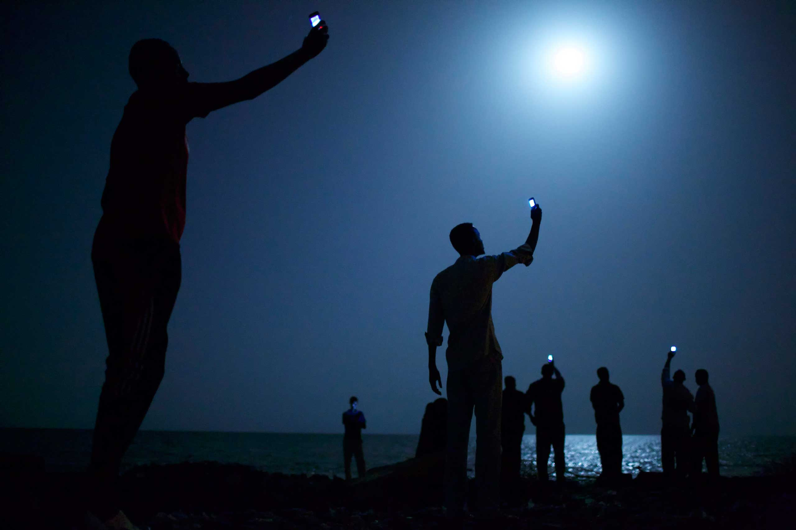 Vogue Italy: Interview with John StanmeyerSomalis wave their mobile phones doing what is known among locals as 'catching,' in an attempt to catch or pickup the mobile phone tower in neighboring Somalia as they stand on Khorley Beach, also called Dead Water Beach, in Djibouti City, Djibouti, Feb. 26, 2013.
