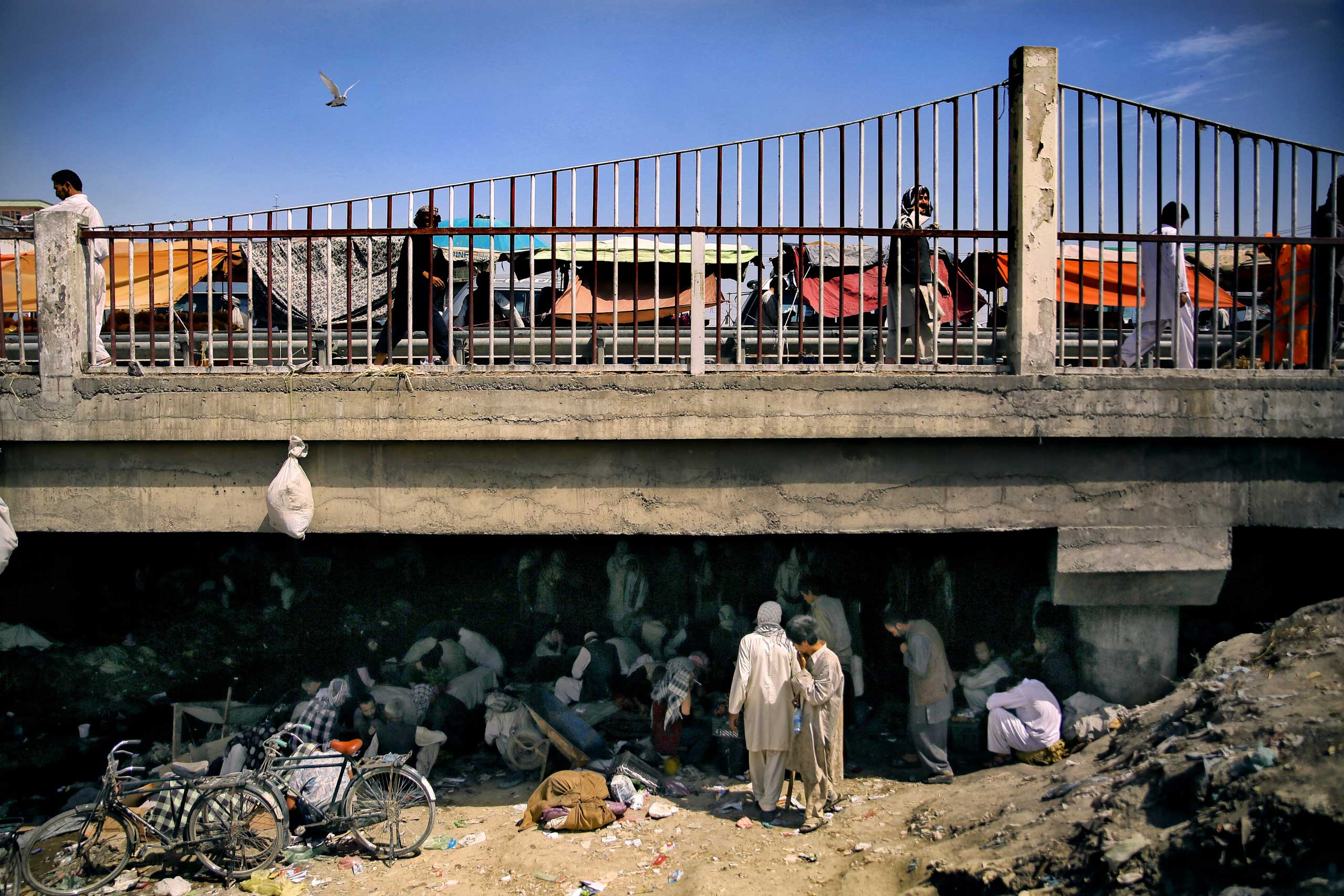 A view of Pul-e Sukhta bridge from the banks of the dried Kabul river on Aug. 26, 2014. While hundreds often thousands of addicts swarm below in a self-fueling network of drugs, crime and despair, life seems to continue unaffected above.