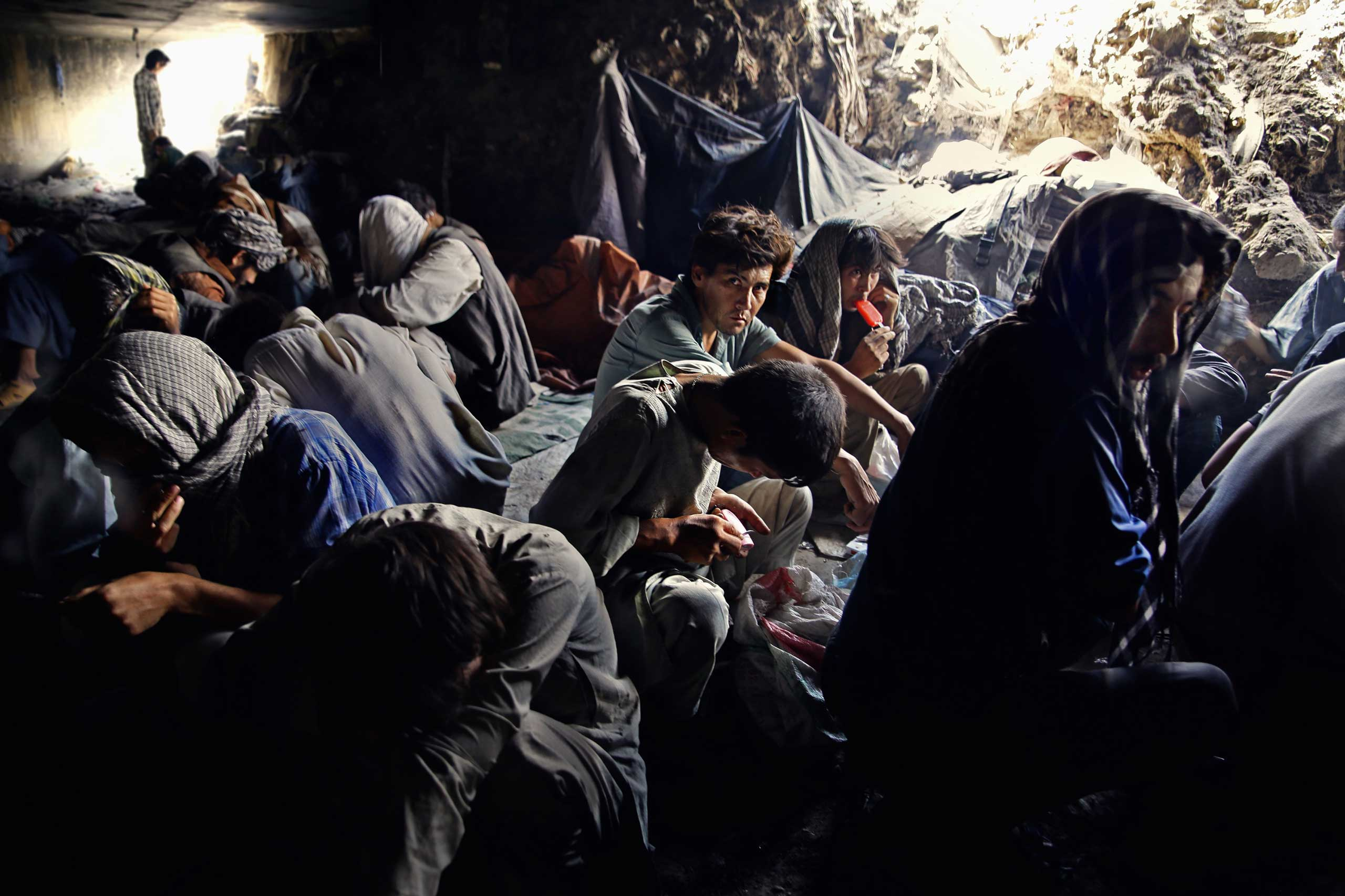 Addicts under the Pul-e Sukhta bridge sheltering from the burning summer sun above on Aug. 26, 2014.