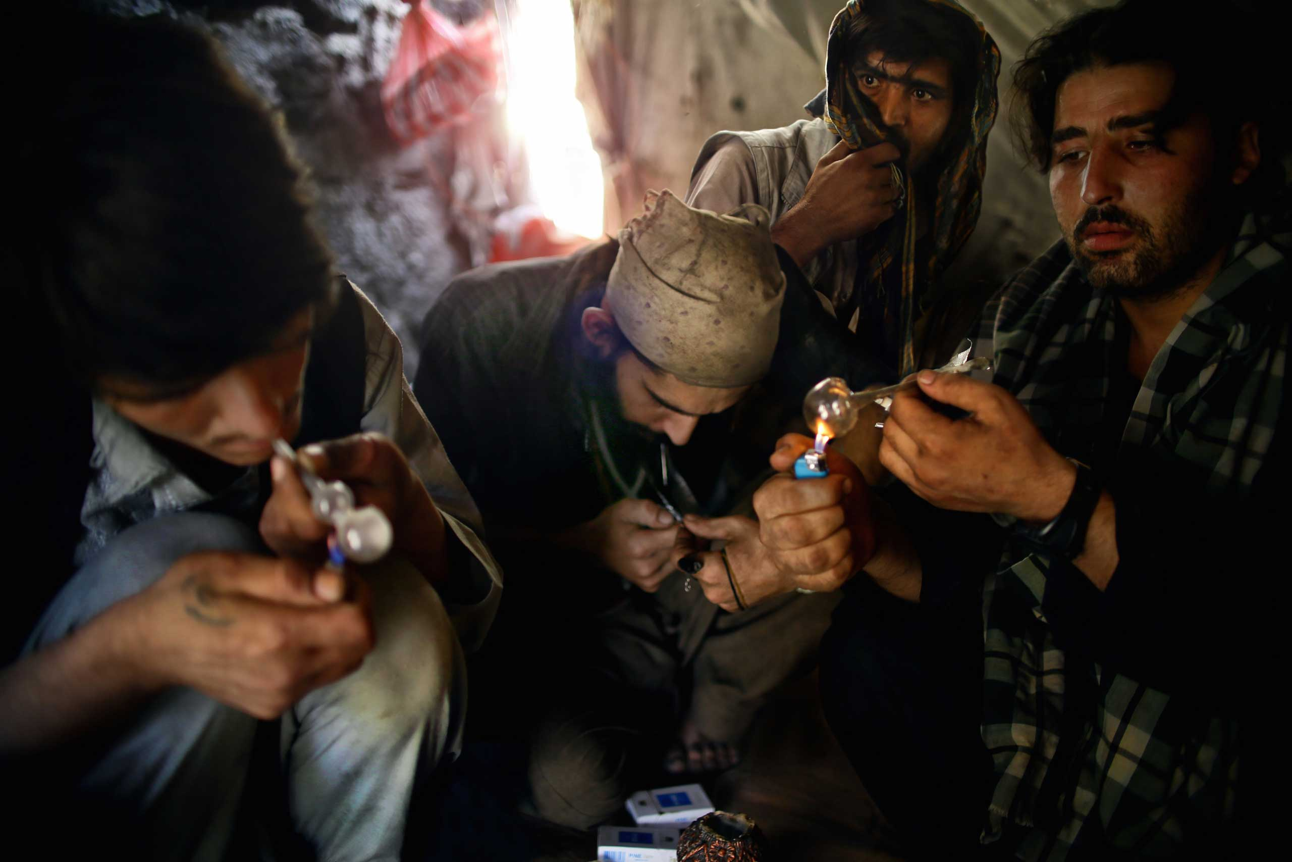 Beneath the Pul-e Sukhta bridge in Western Kabul a group of Pakistani heroin addicts take refuge from the summer sun on July 26, 2014.