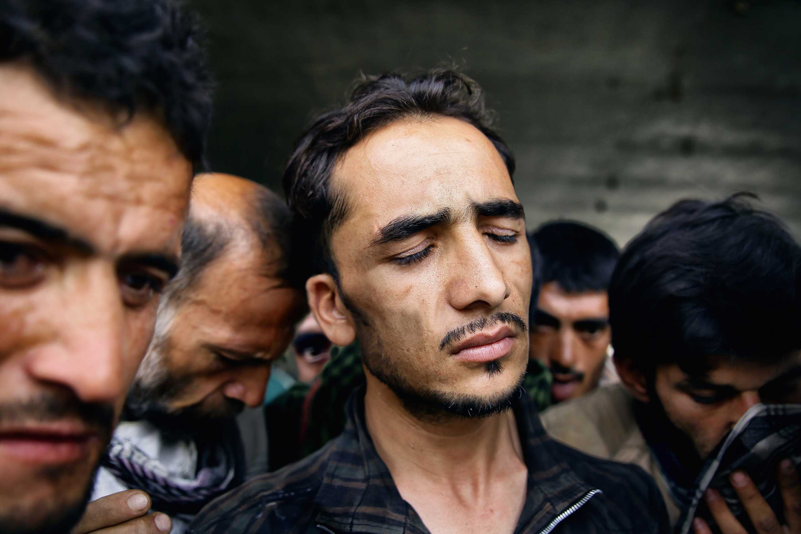 Abdul Rahim Qadl grimaces in a haze after smoking a hit of opium resin under Pul-e Sukhta bridge, Kabul on Aug. 1, 2014.