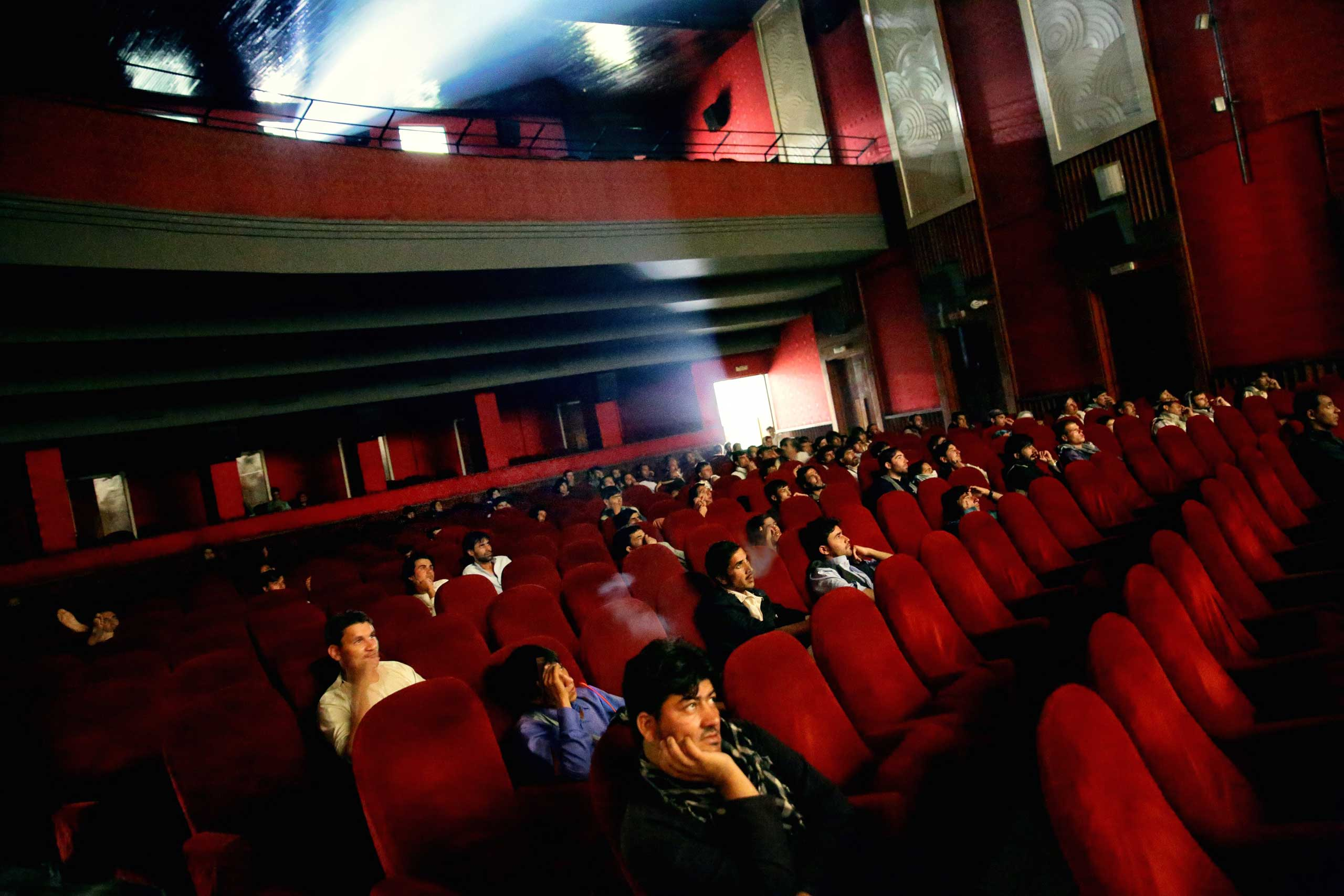 Young men smoke hashish and watch a Bollywood film at the recently refurbished Cinema Ariana in central Kabul on Aug. 18, 2014.