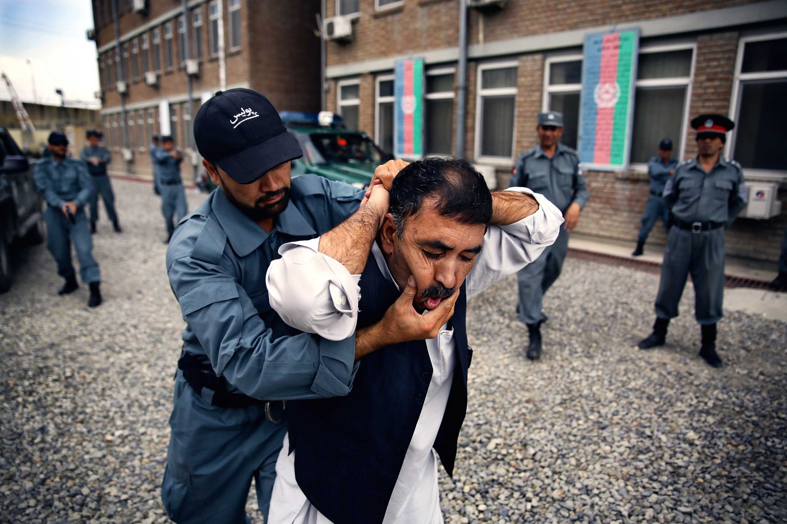 Afghan National Police officers from the Anti-Narcotics Quick Reaction Force (ANQRF) carry out a brutal stop and search scenario exercise intended for drug traffickers at a training centre in Kabul on Aug. 25, 2014.