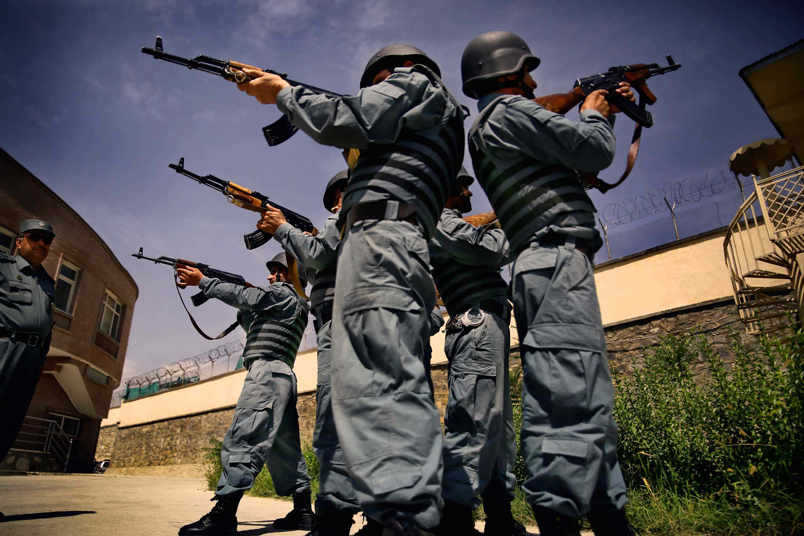 Afghan National Police officers from the Anti-Narcotics Quick Reaction Force (ANQRF) aim back-to-back holding Kalashnikov rifles as they performs exercises at a training centre in Kabul on Aug. 26, 2014.
