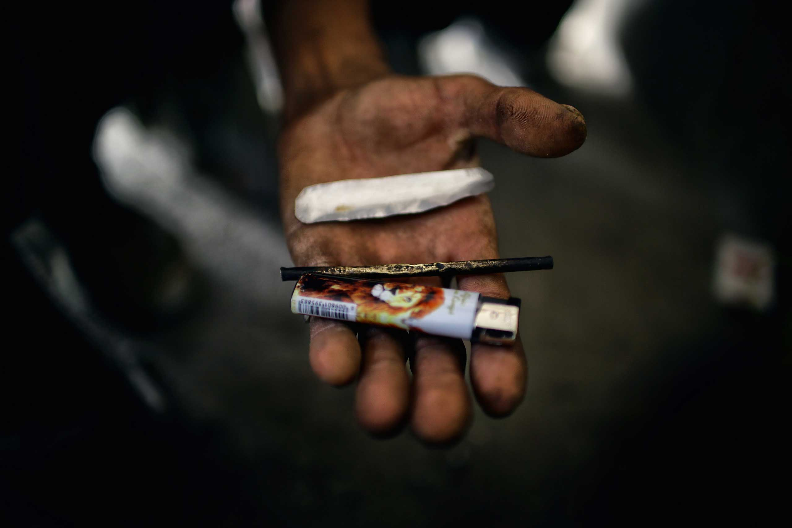 An addict below the Pul-e Sukhta bridge in Western Kabul reveals his instruments for smoking opium resin and heroin on July, 26, 2014.