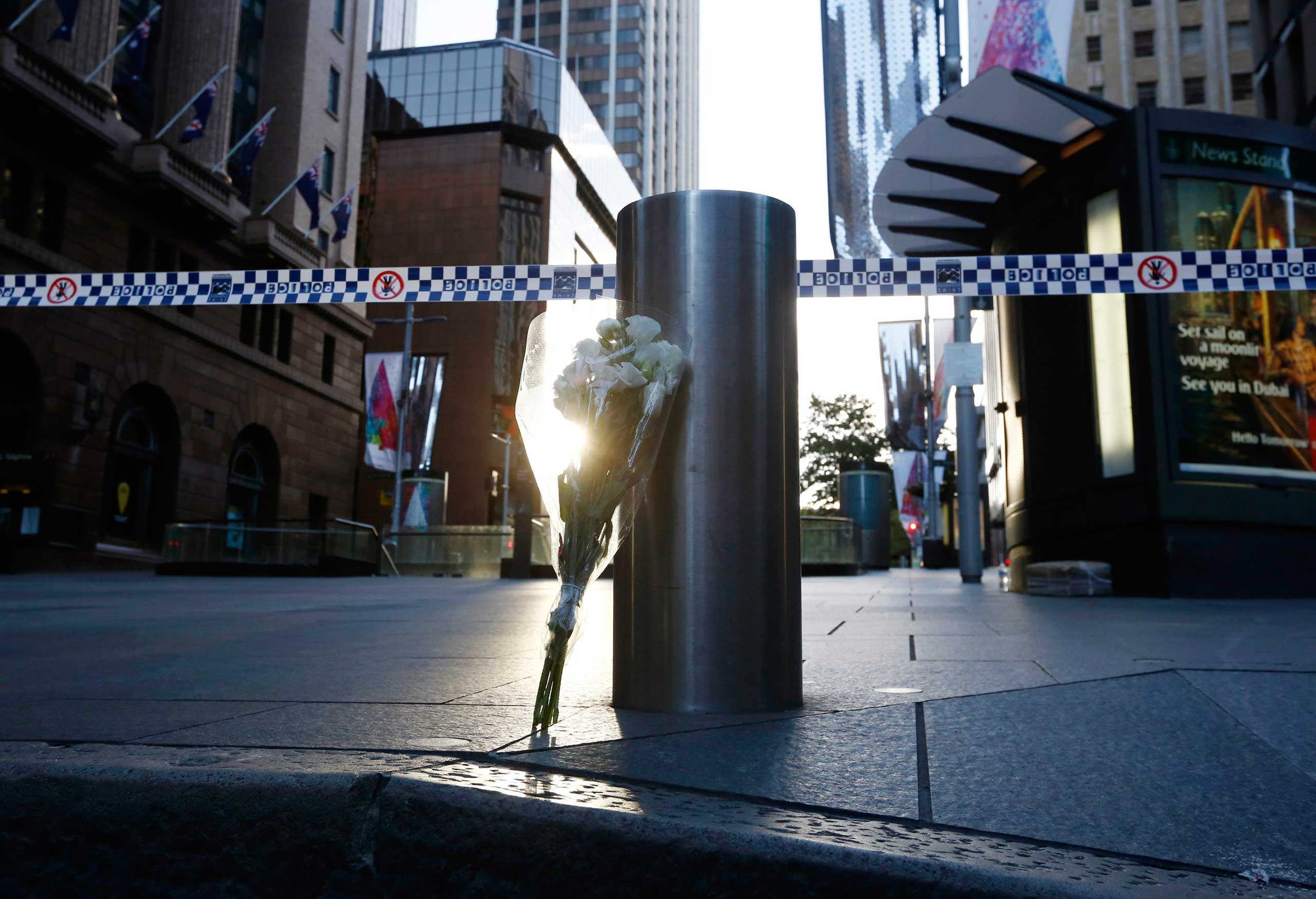 A bouquet is pictured under police tape near the cordoned-off scene of a hostage taking at Martin Place after it ended, early on Dec. 16, 2014.