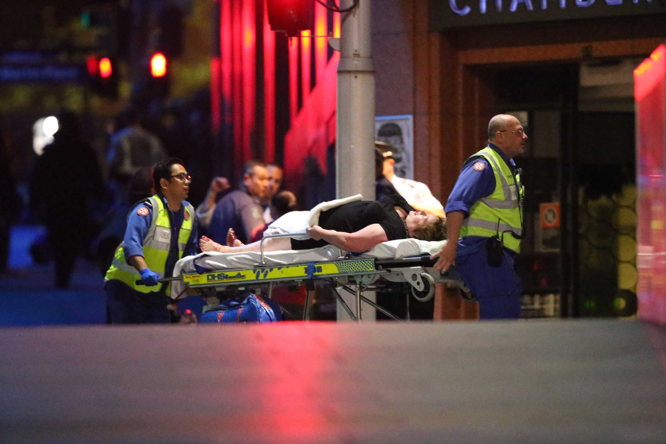A injured hostage is wheeled to an ambulance after shots were fired during  a cafe  siege at Martin Place in the central business district of Sydney, Dec. 16, 2014.