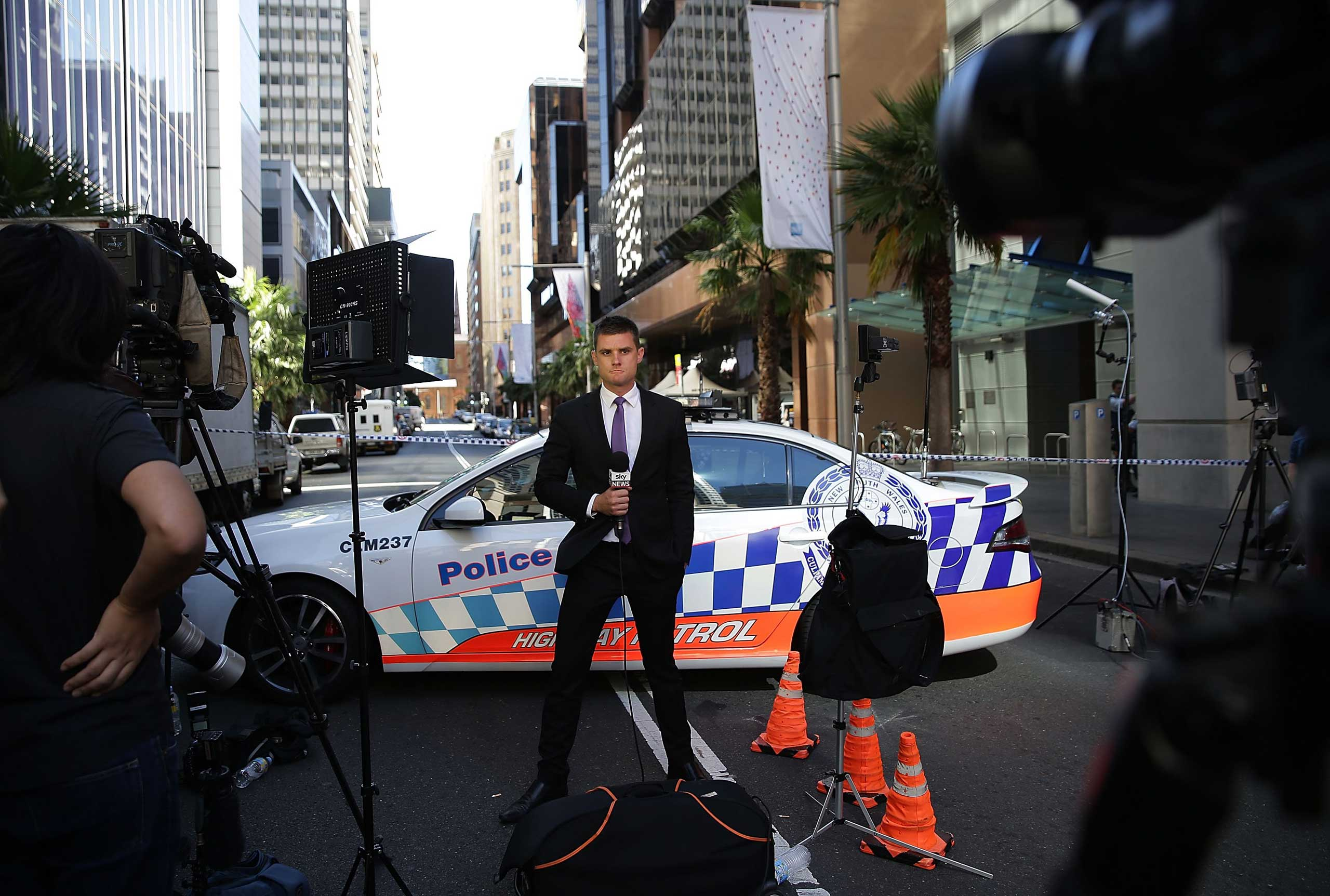 A TV presenter does a live cross from Phillip St on Dec. 15, 2014 in Sydney.