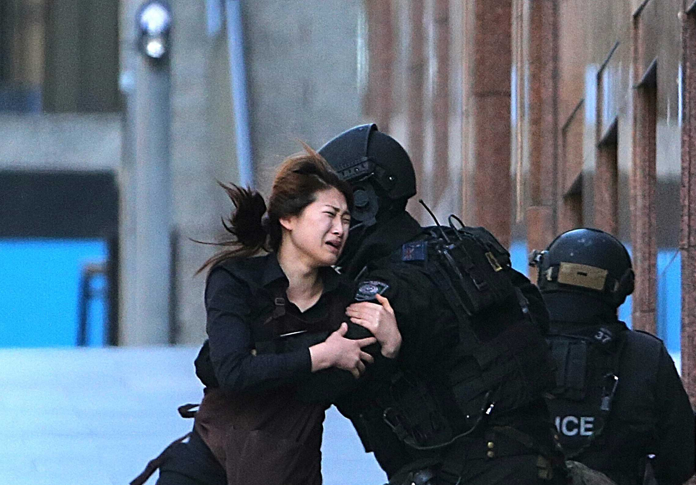 A hostage runs to armed tactical response police officers for safety after she escaped from a cafe under siege at Martin Place in the central business district of Sydney, Dec. 15, 2014.
