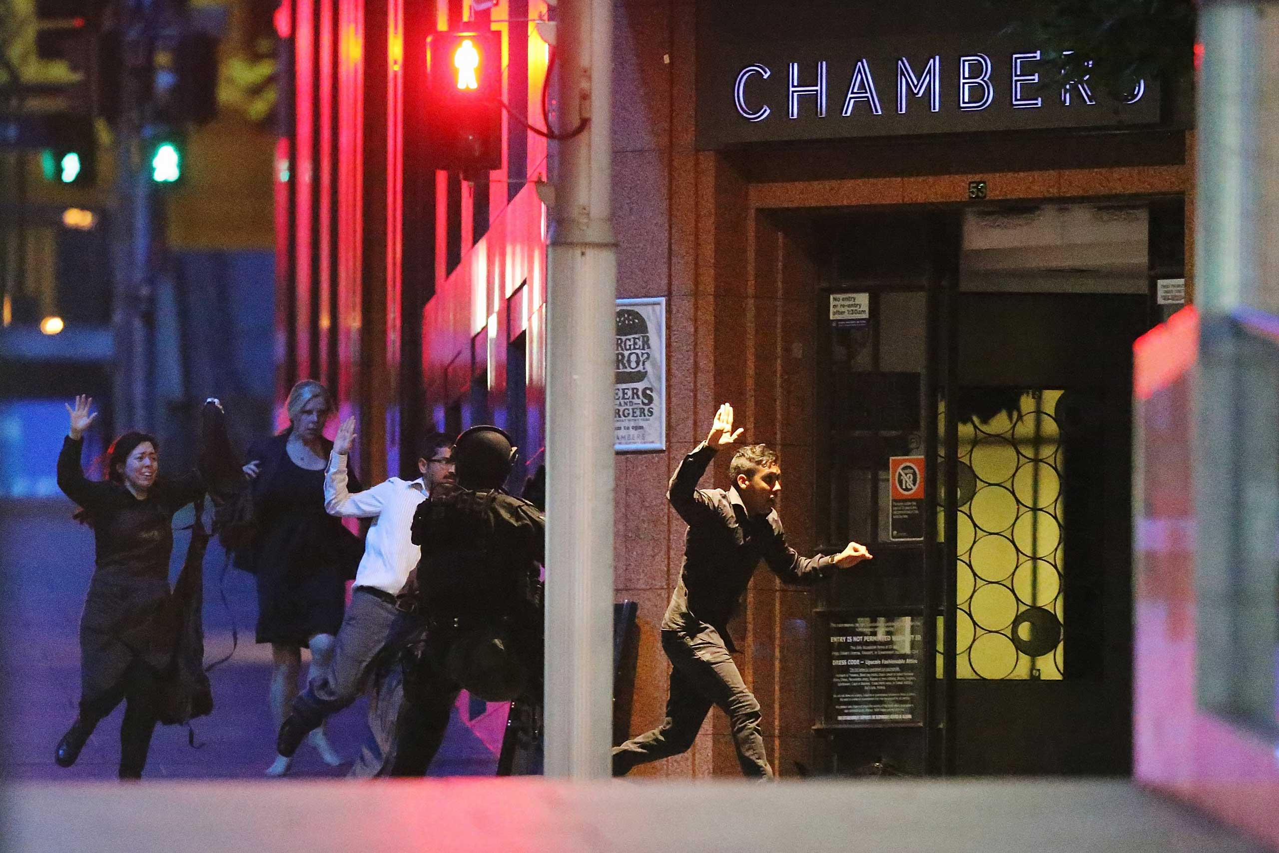 People run with their hands up from the Lindt Cafe, Martin Place during a hostage standoff on Dec. 15, 2014 in Sydney.
