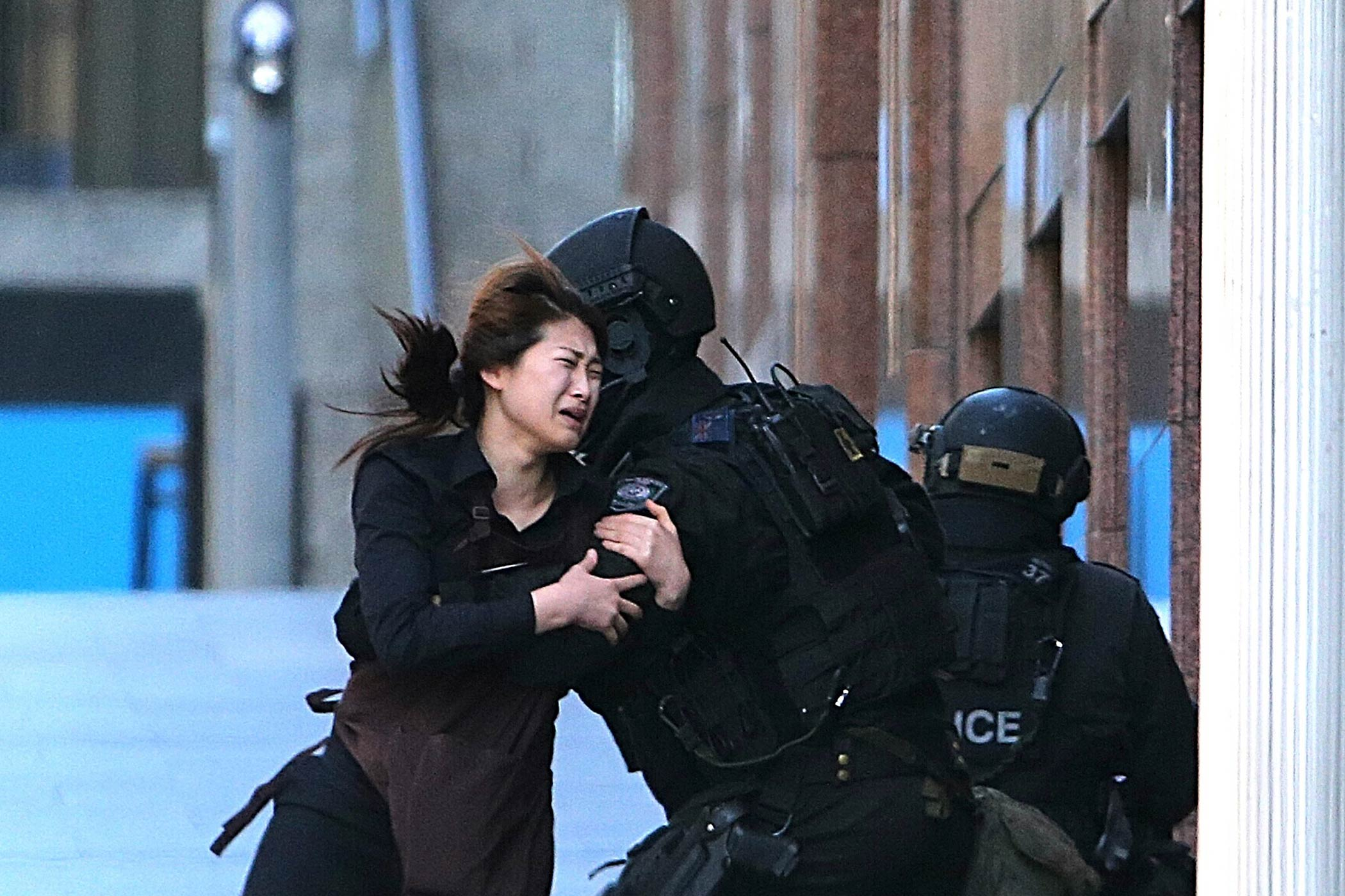 A hostage runs to tactical response police officers for safety after she escaped from a cafe under siege at Martin Place in Sydney, Australia, on Dec. 15, 2014.