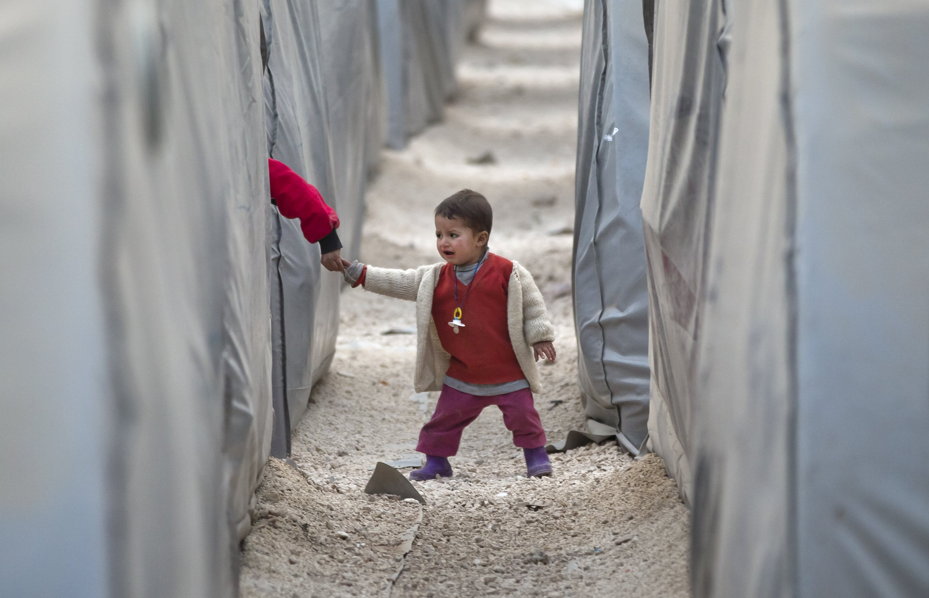 A Syrian Kurdish refugee child from the Kobani area holds another's hand as he walks between tents at a camp in Suruc, on the Turkey-Syria border on Nov. 14, 2014.