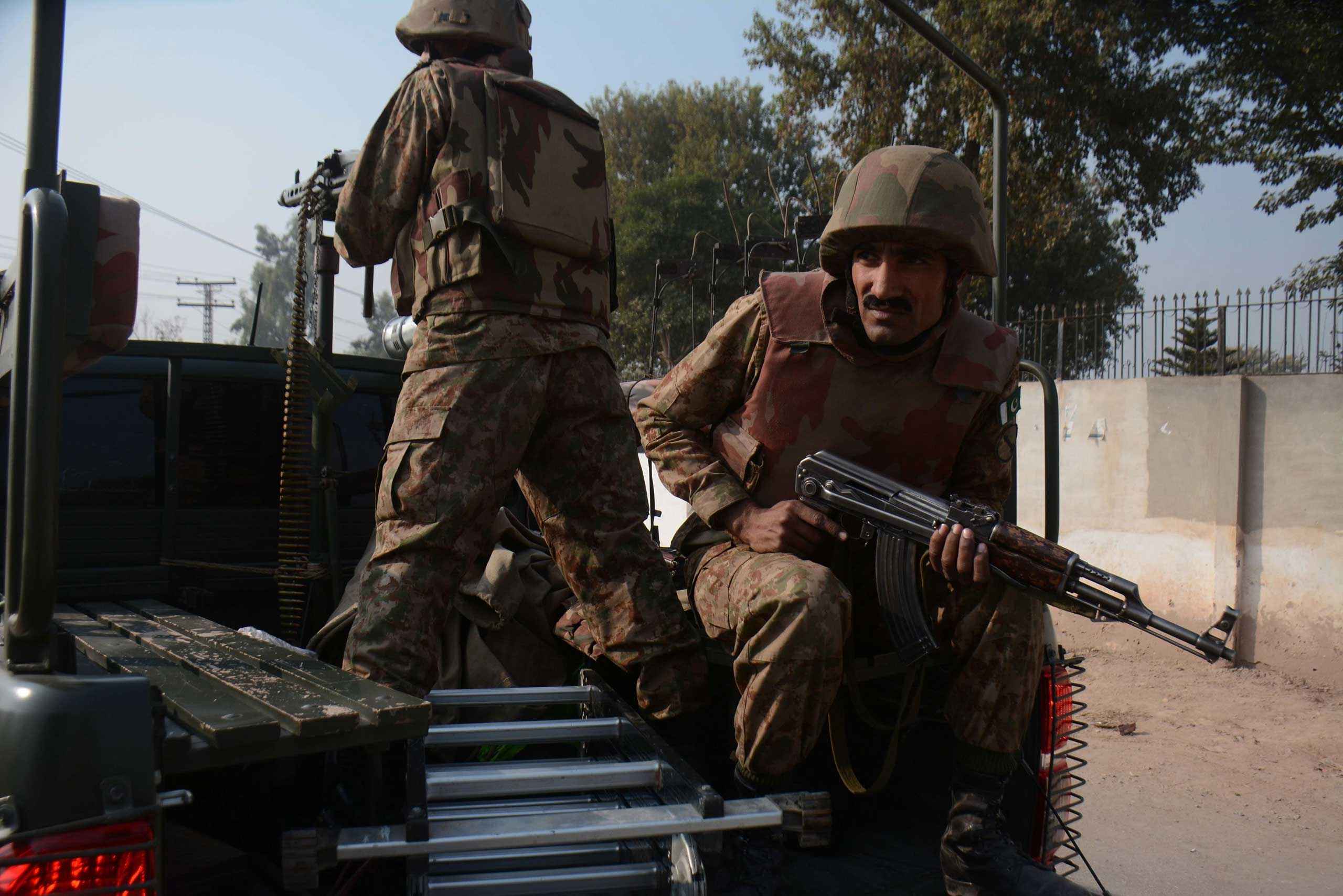 Pakistani security forces take positions following a Taliban attack at an Army run school, in Peshawar, on Dec. 16, 2014.