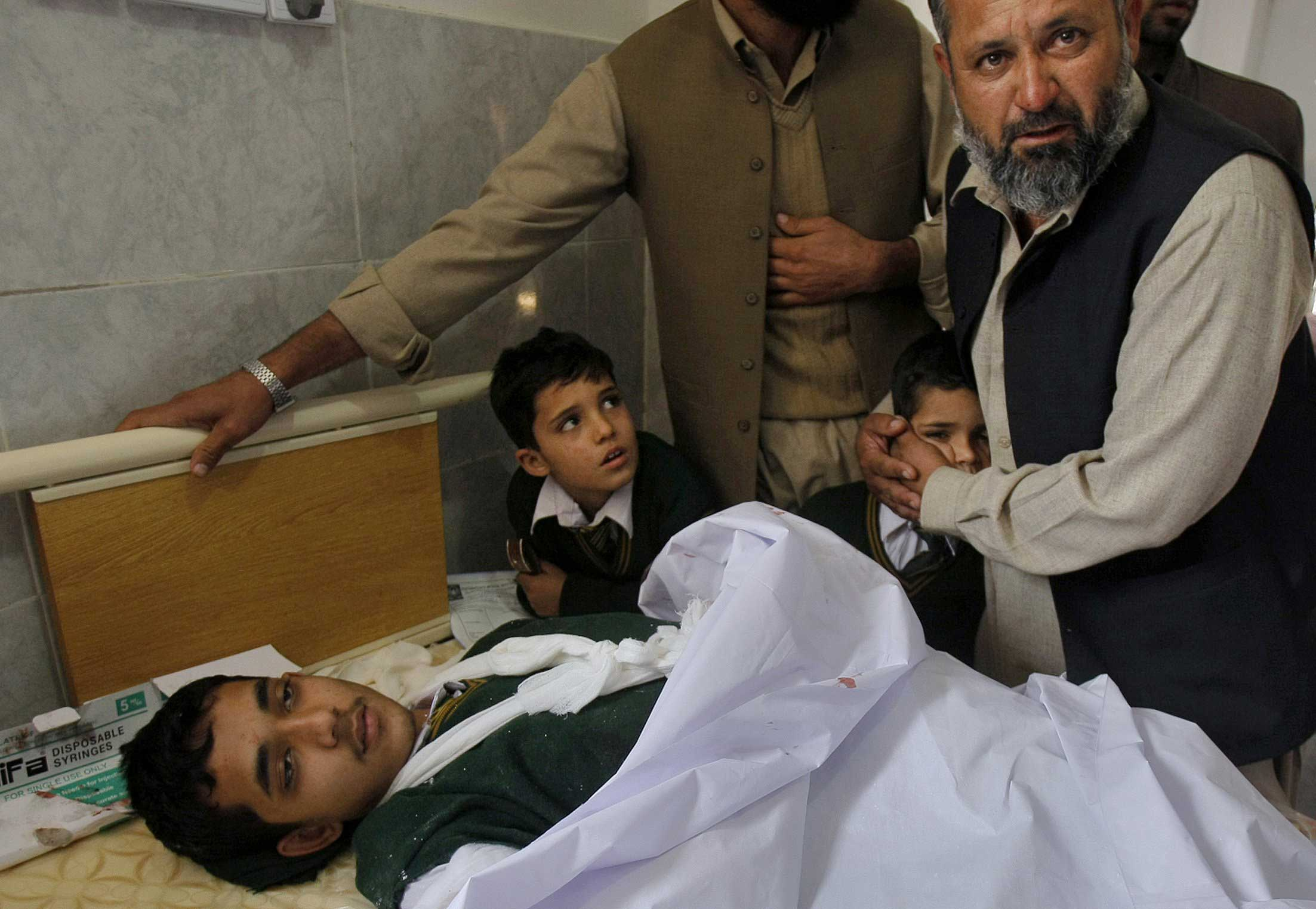 A Pakistani man comforts a child standing at the bedside of a boy who was injured in a Taliban attack on a school, at a local hospital in Peshawar, Dec. 16, 2014.