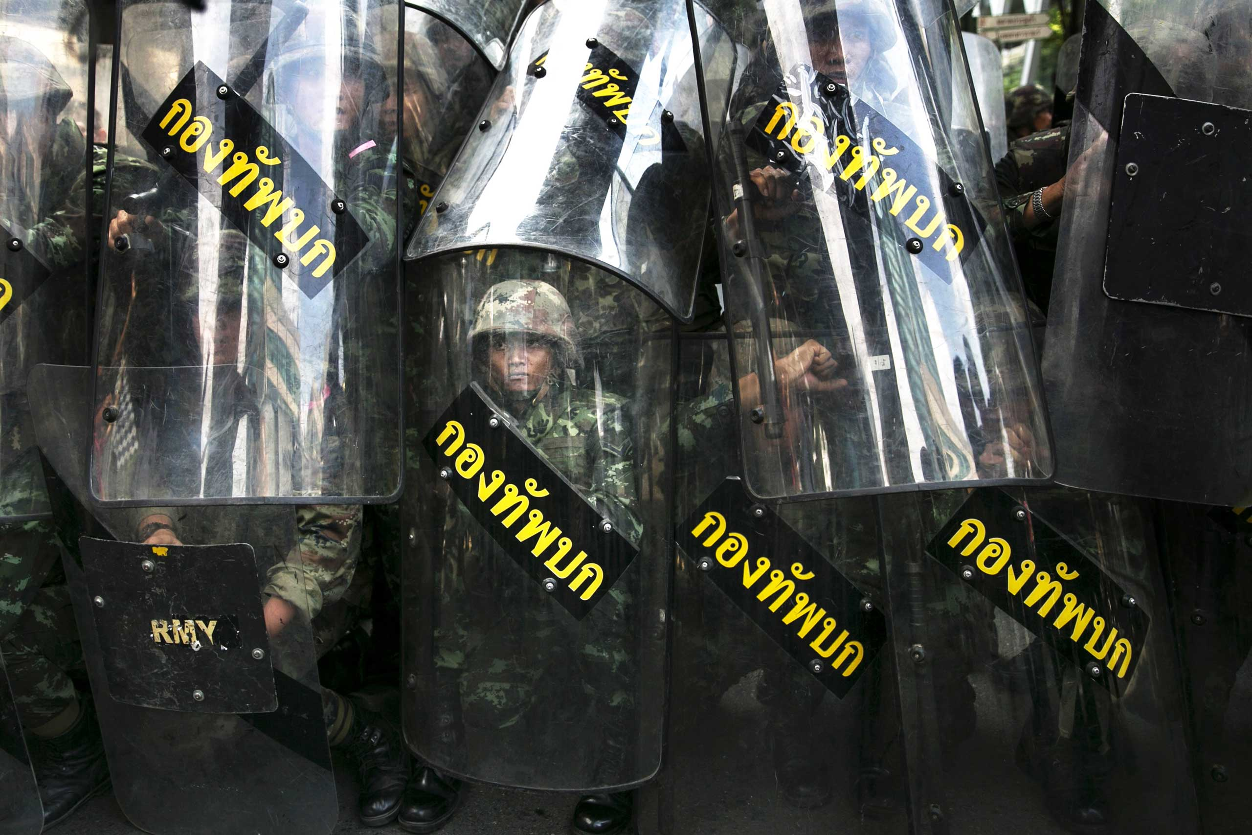 Thailand:  Anti-coup protestThai military stand behind their riot shields as protesters threaten them during an anti-coup protest on the third day of the military coup May 25, 2014 in Bangkok.