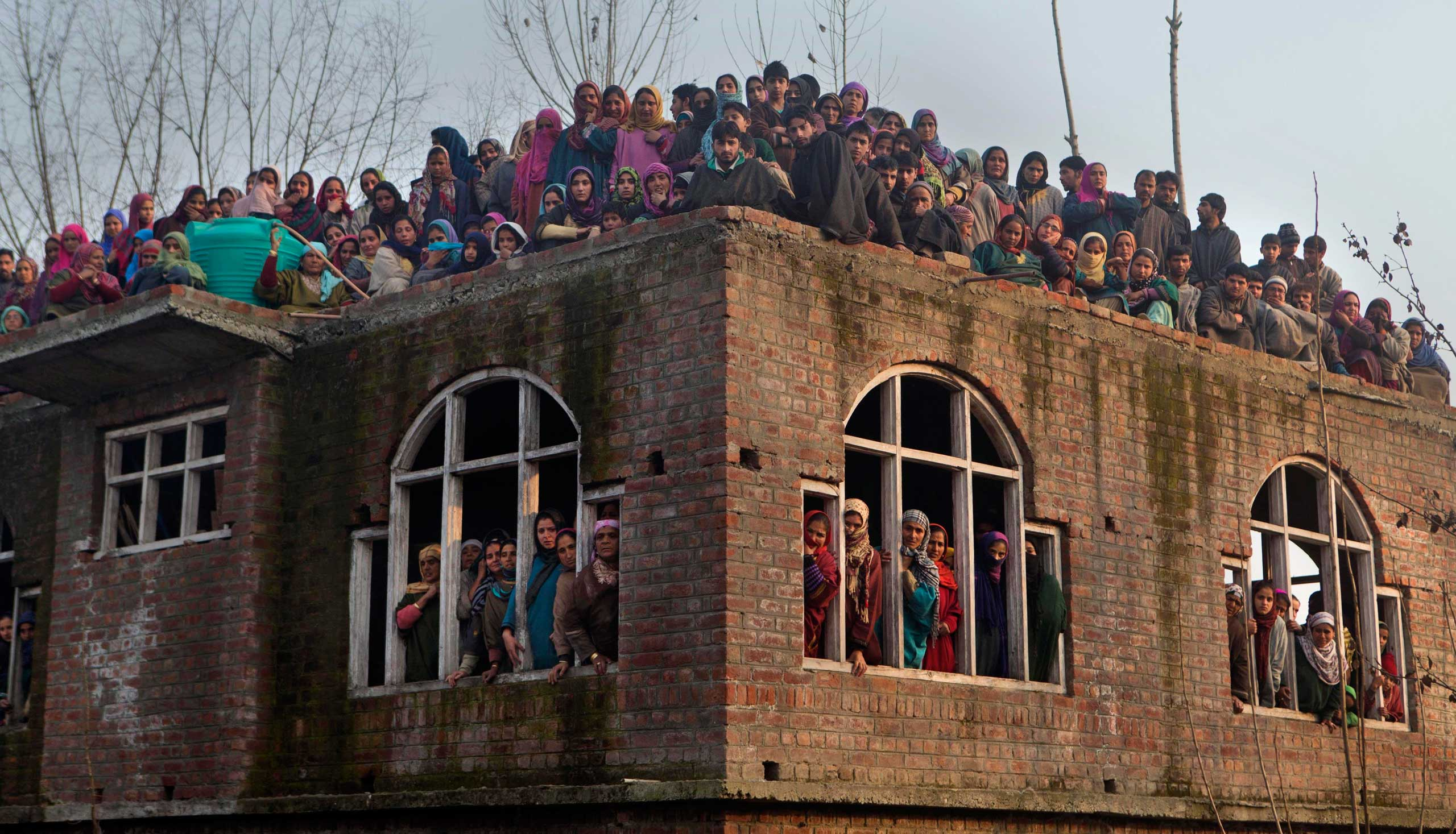 Dec. 3, 2014. Kashmiri Muslims watch the funeral procession of Indian paramilitary soldier Muhammad Shafi Bhat in Buran, north of Srinagar, India. Thousands took part in the procession after Shafi was killed in an attack by Maoist rebels in central India.