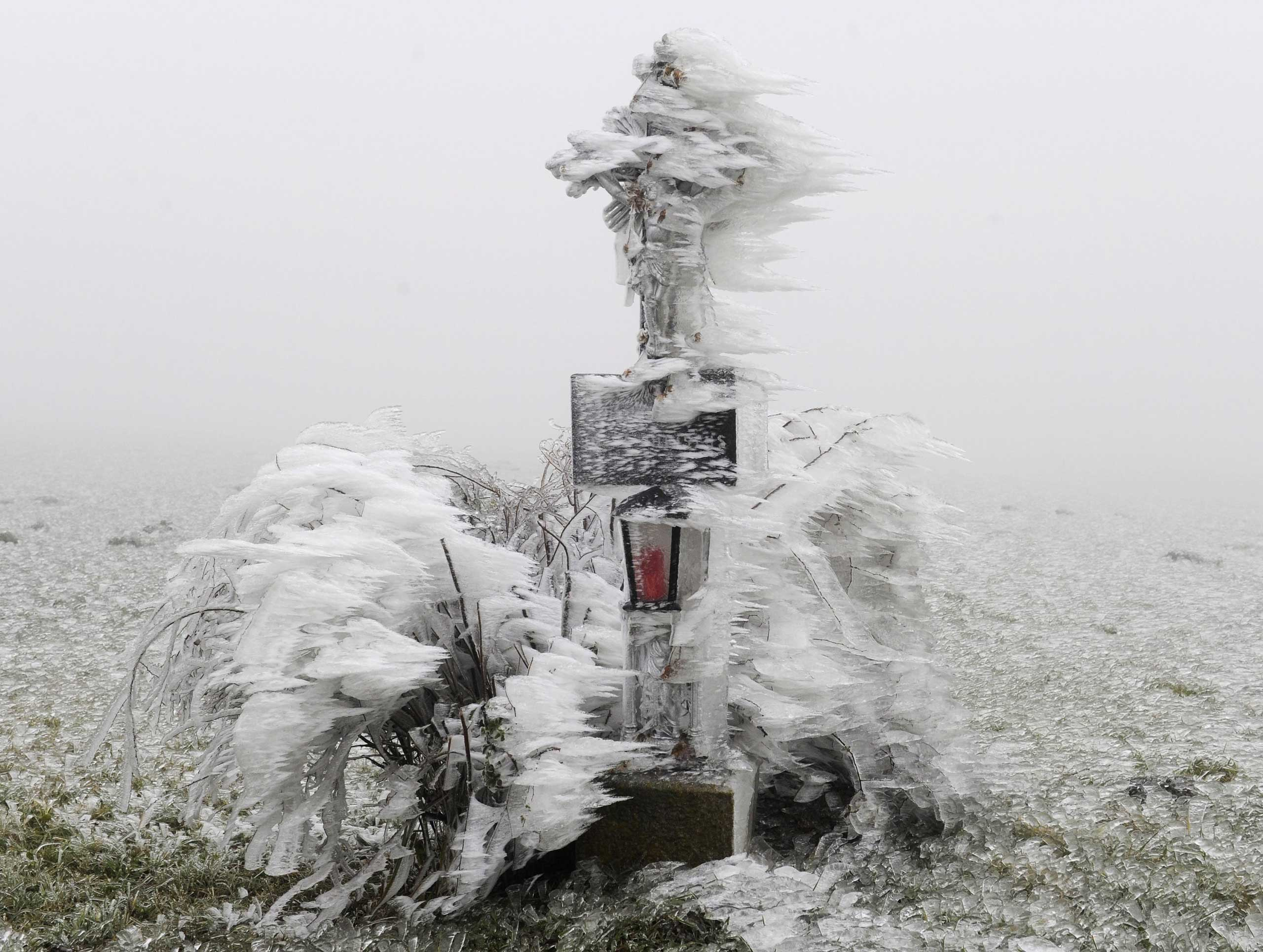 Dec. 02, 2014. A frozen memorial cross is seen near Ottenschlag in the state of Lower Austria. Frost and sleet have caused a number of roadblocks due to broken trees throughout parts of Austria.