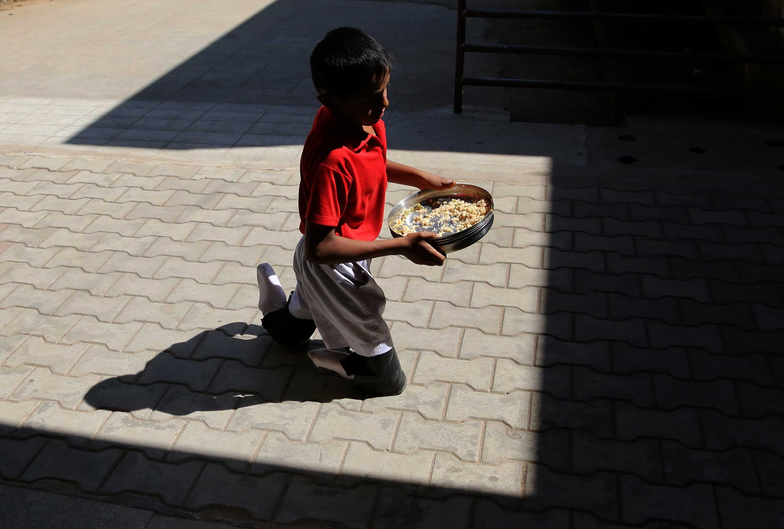 Dec. 3, 2014. A disabled child carries plates after having his lunch at the Association of People with Disability run school in Bangalore, India, on the International Day of Persons with Disabilities.