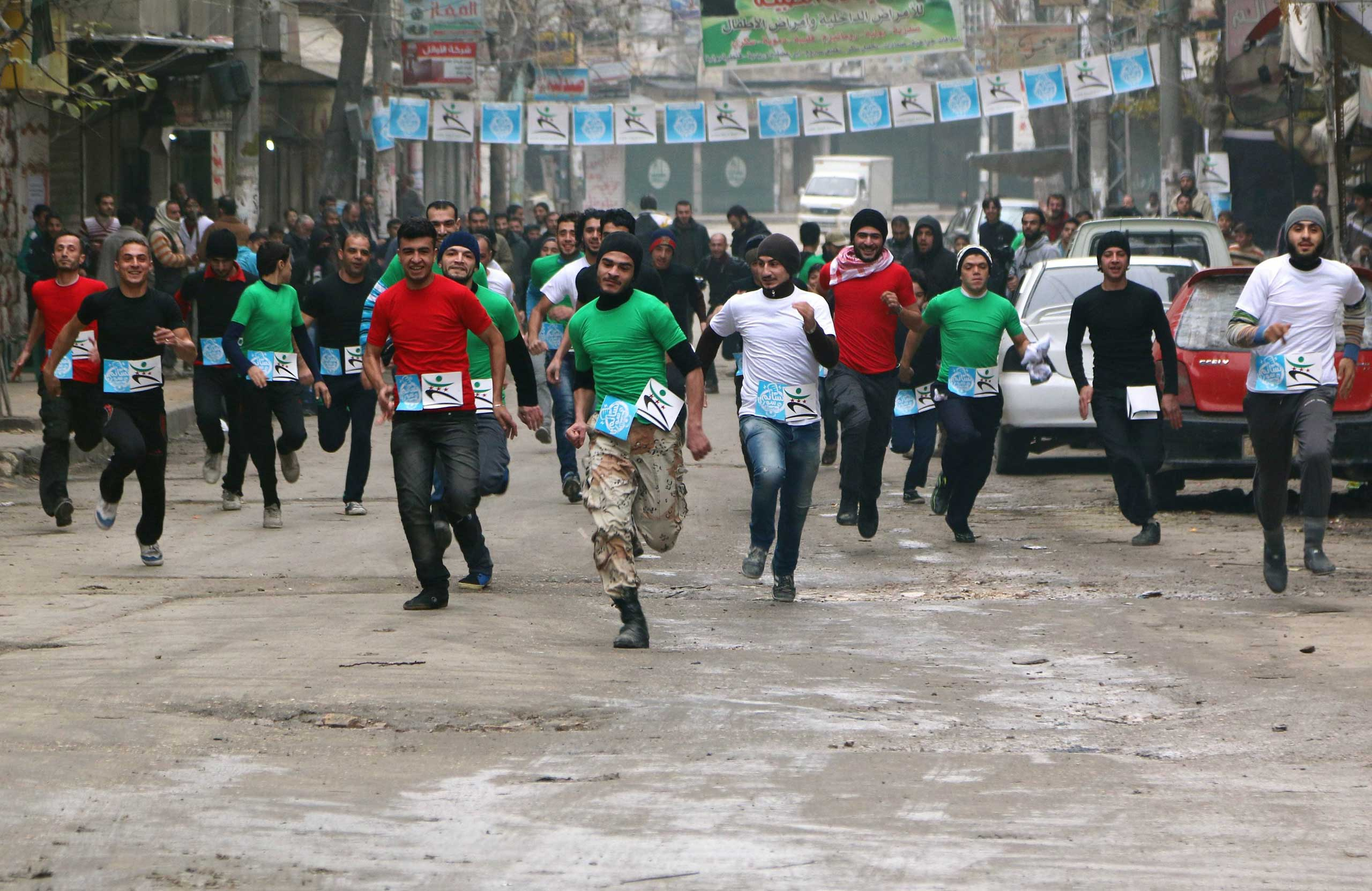 Dec. 2, 2014. Participants compete in a running race along a street in Aleppo's Bustan al-Qasr neighborhood, a rebel-controlled area in Syria.
