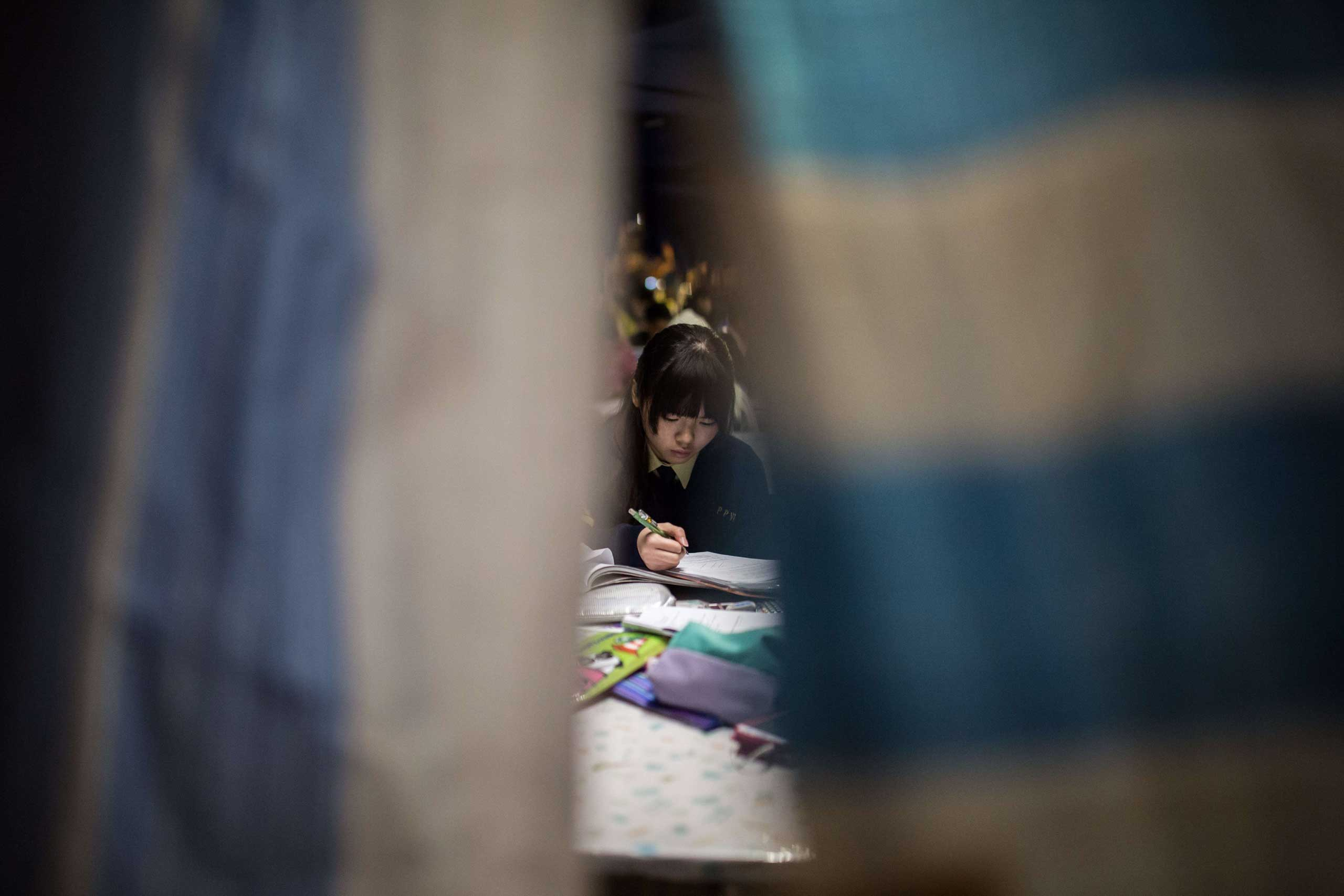 Dec. 1, 2014. A young student studies in a makeshift classroom set up on a main road at a major pro-democracy protest site in the Admiralty district of Hong Kong.