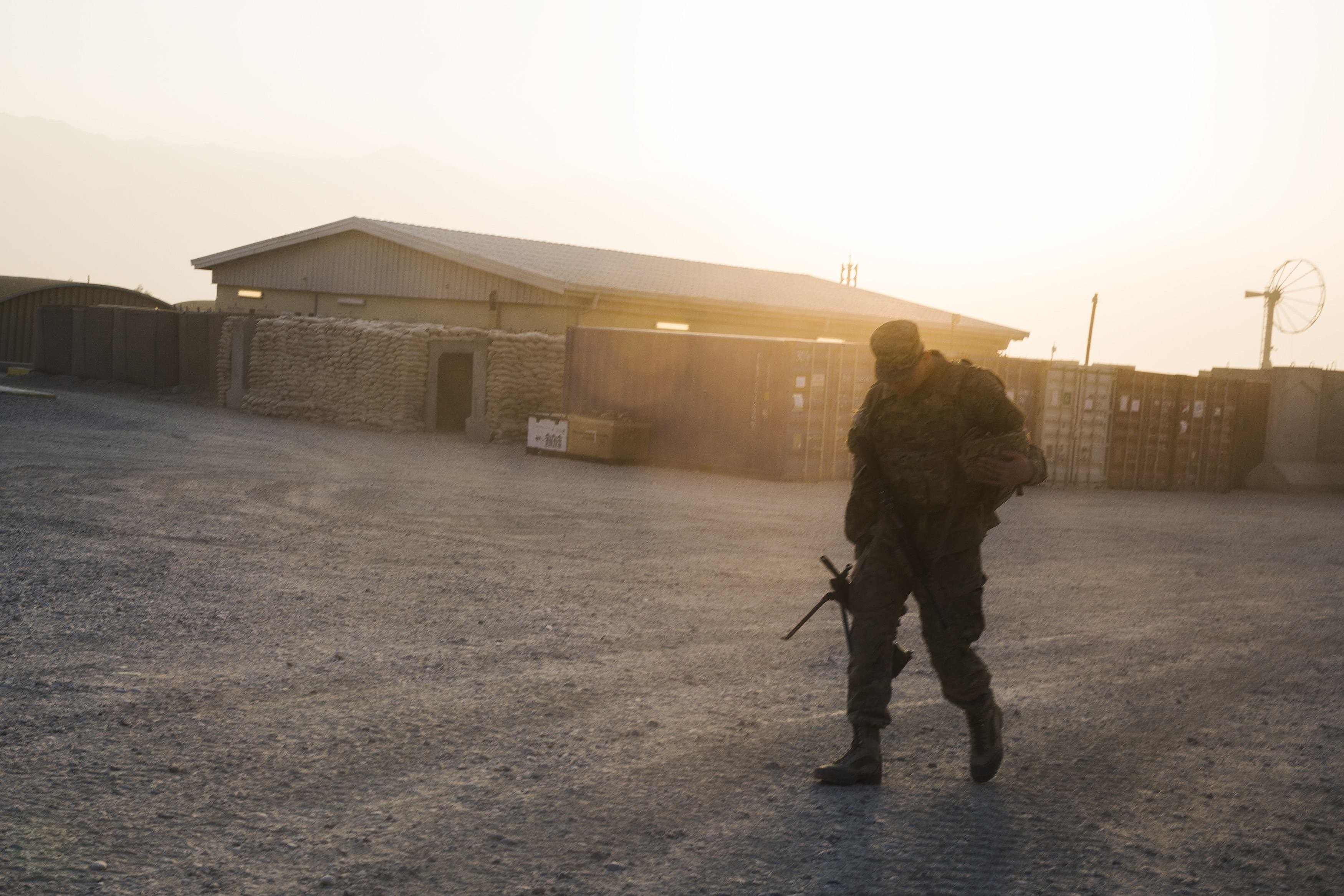 A U.S. soldier from the 3rd Cavalry Regiment walks with his rifle, after returning from a mission at forward operating base Gamberi, in the Laghman province of Afghanistan, Dec. 15, 2014.