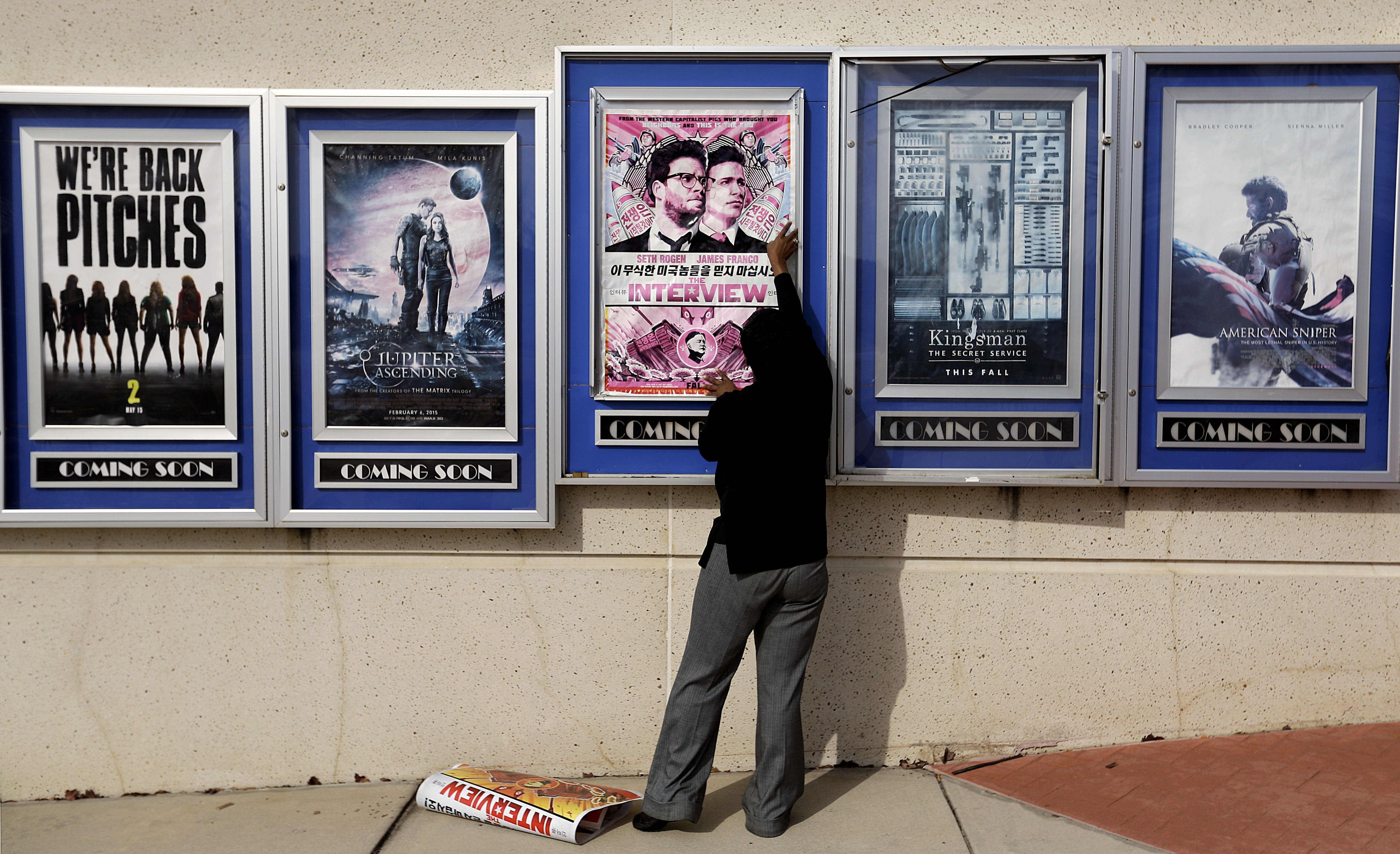A poster for the movie The Interview is taken down by a worker after being pulled from a display case at a Carmike Cinemas movie theater on Dec. 17, 2014, in Atlanta