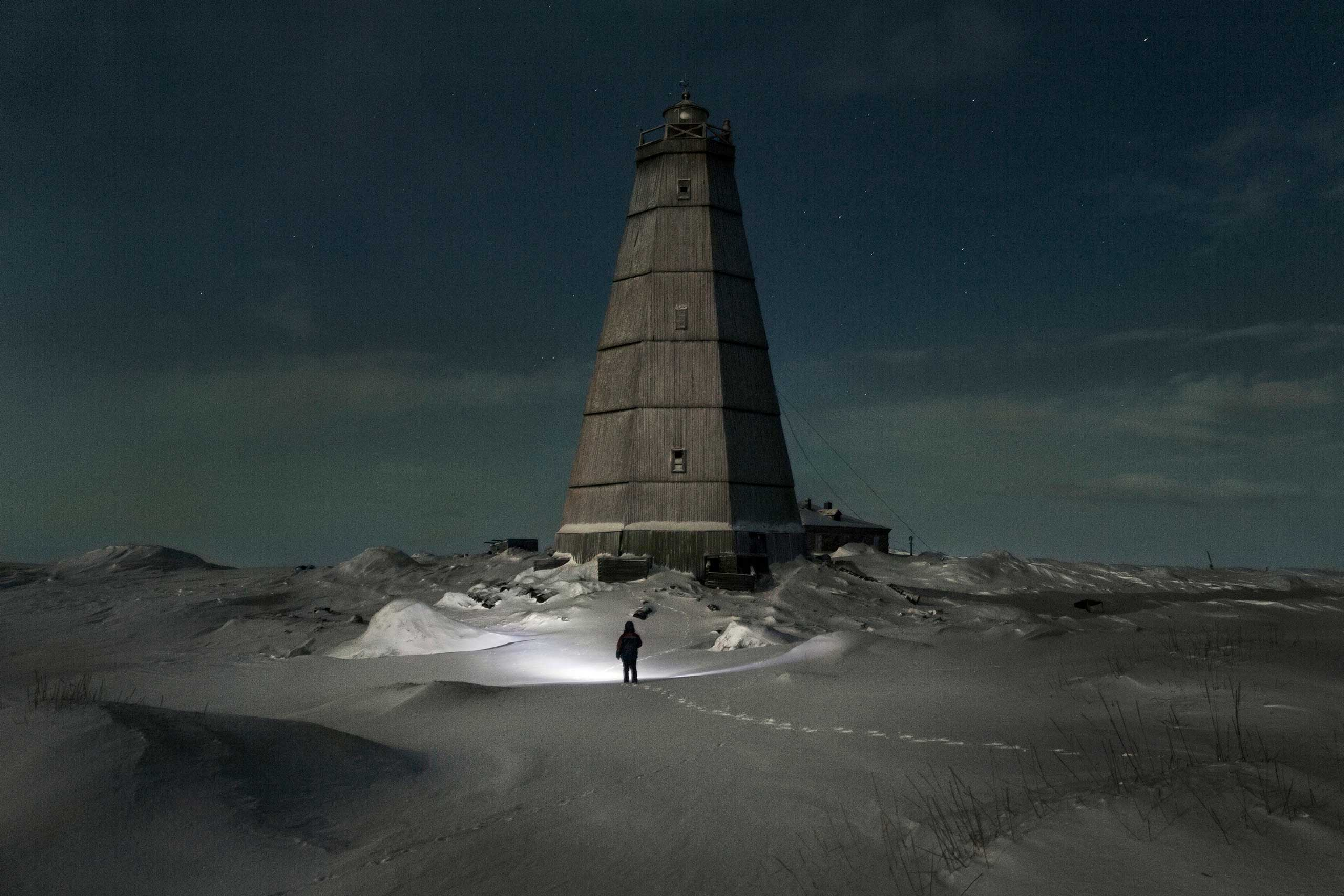 The New Yorker: Weather ManVyacheslav Korotki walks out under a full moon to an abandoned lighthouse that used to serve the Northern Sea Route, to gather firewood to help heat his home. Khodovarikha, Russia.