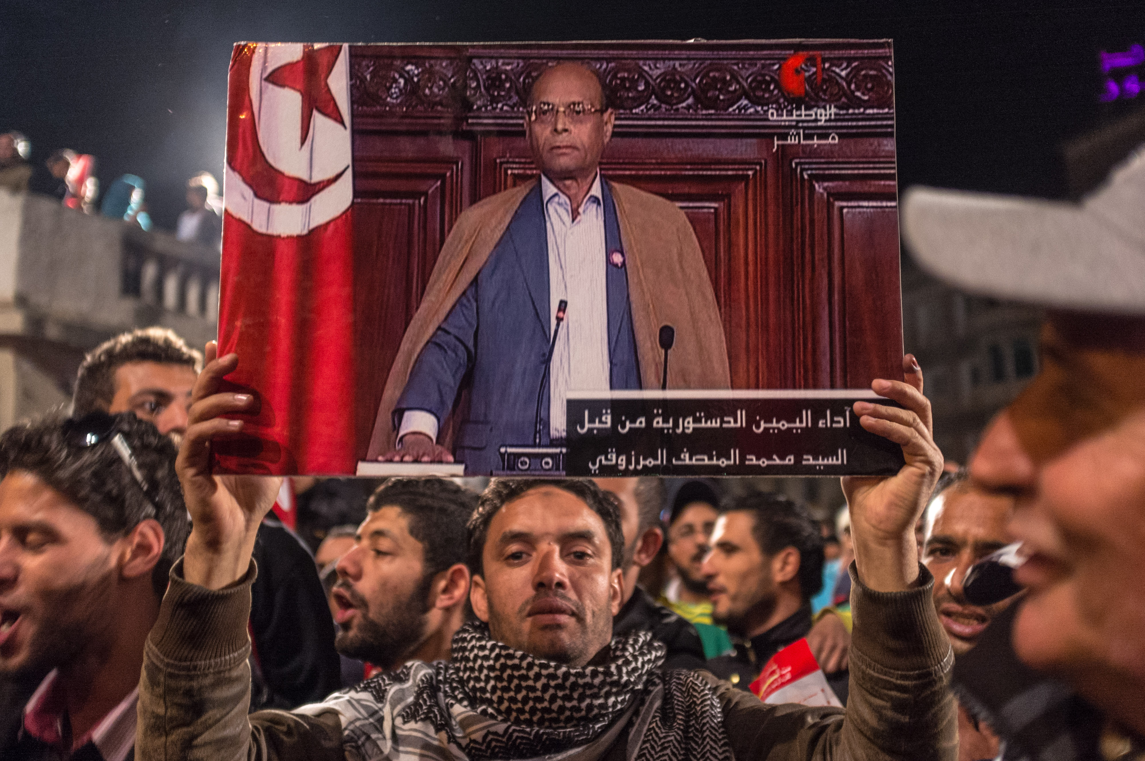 A man holds up a picture of Tunisian presidential candidate Moncef Marzouki, as supporters gather to hear his speech after the second round of the country's presidential election, in Tunis, Sunday, Dec. 21, 2014.