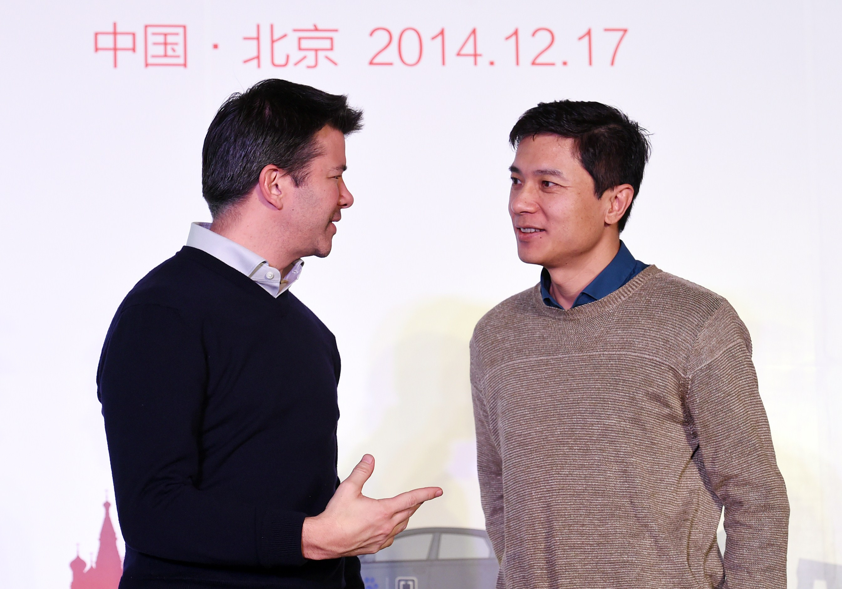 Uber CEO Travis Kalanick (L) and Baidu Chairman and CEO Robin Li at a signing ceremony and press conference in Beijing on Dec. 17, 2014.