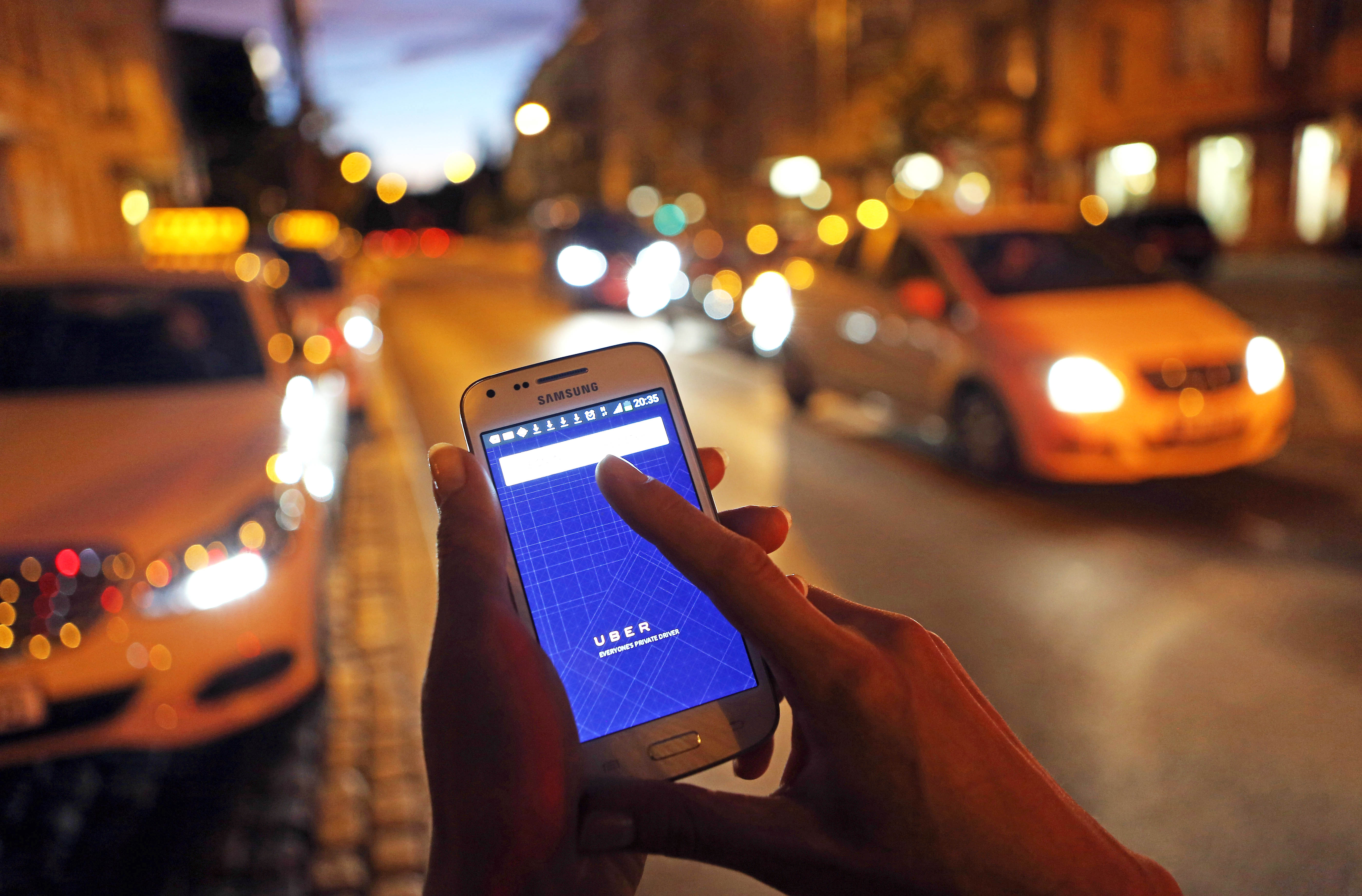 A woman uses the Uber app on an Samsung smartphone on Sept. 2, 2014 in Berlin.