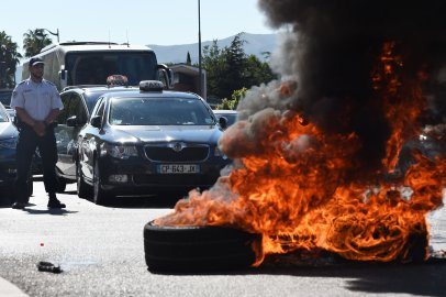 French Taxi drivers burn tires as they protest in the southern city of Marseille on June 25, 2015 as they demonstrate against UberPOP, a popular taxi app that is facing fierce opposition from traditional cabs.