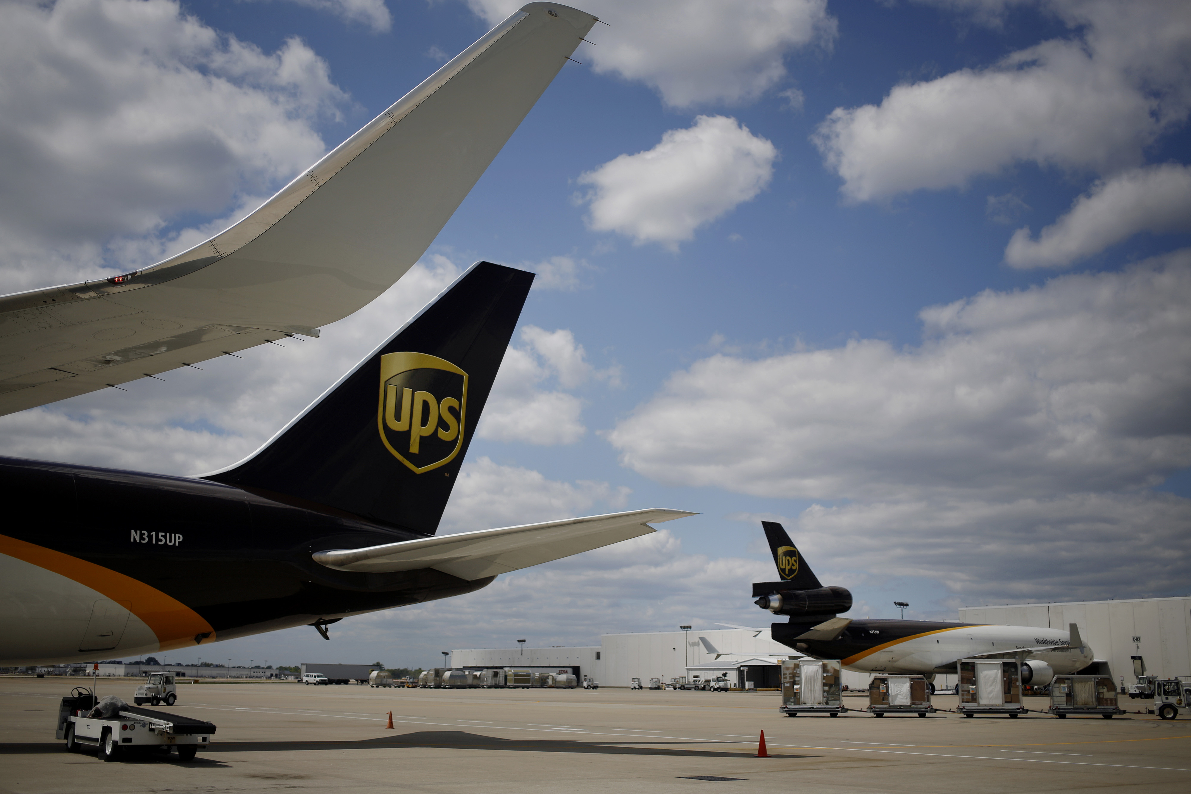UPS jet freighters sit on the tarmac while being loaded with outbound packages during the afternoon sort at the UPS Worldport hub in Louisville, Kentucky on July 24, 2014.