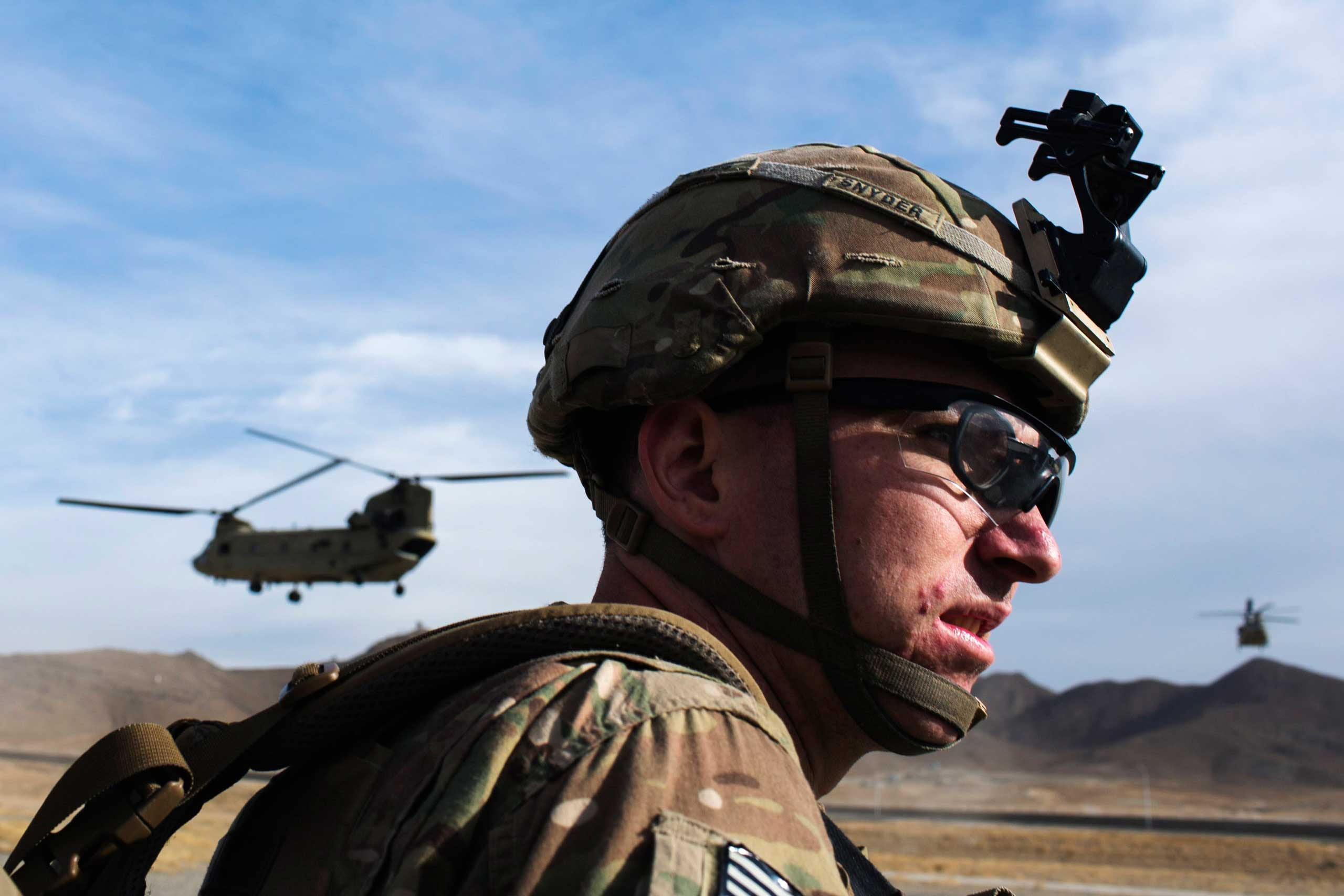 A U.S. soldier from the 3rd Cavalry Regiment waits for a CH-47 Chinook helicopter after an advising mission at the Afghan National Army headquarters for the 203rd Corps in the Paktia province of Afghanistan on Dec. 21, 2014.