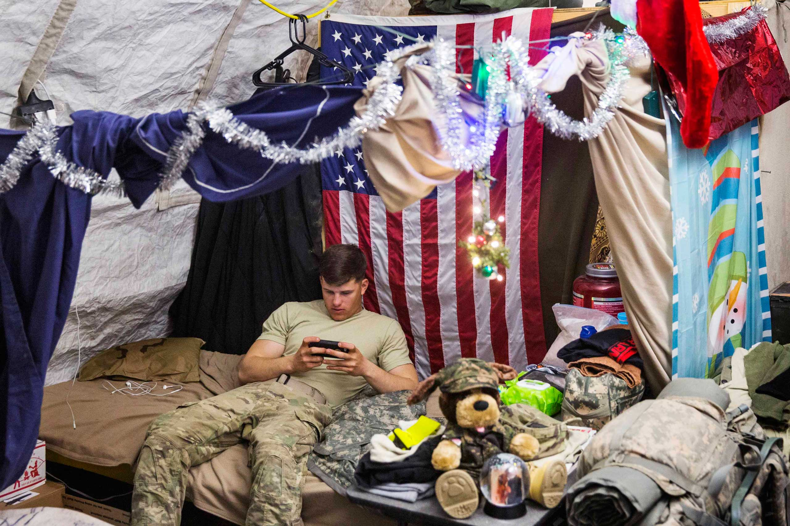 A U.S. soldier from the 3rd Cavalry Regiment relaxes in his quarters after taking part in a mortar exercise on forward operating base Gamberi in the Laghman province of Afghanistan on Dec. 24, 2014.
