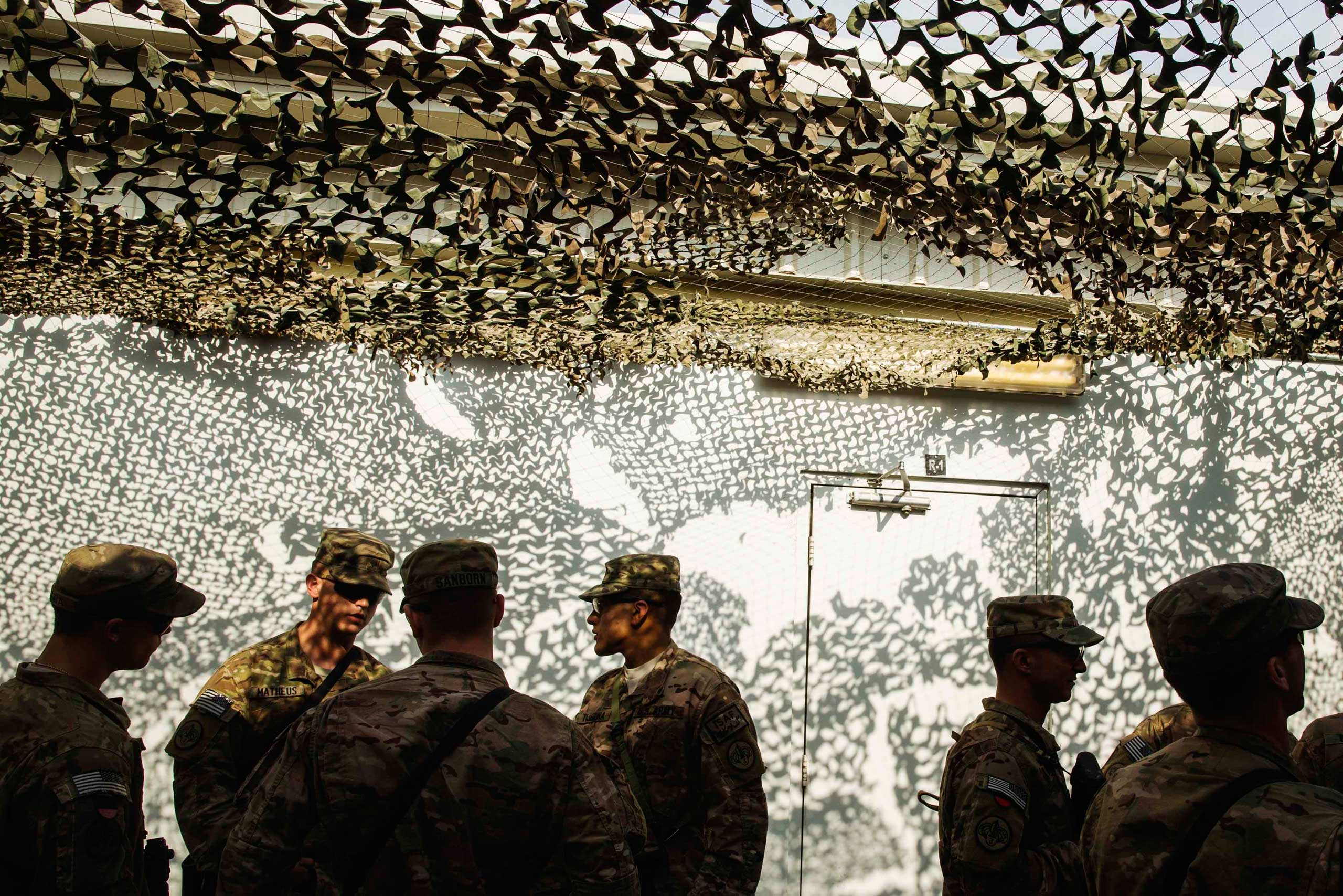 U.S. soldiers from the 3rd Cavalry Regiment wait in line to get food during a Christmas day lunch at forward operating base Gamberi in the Laghman province of Afghanistan on Dec. 25, 2014.