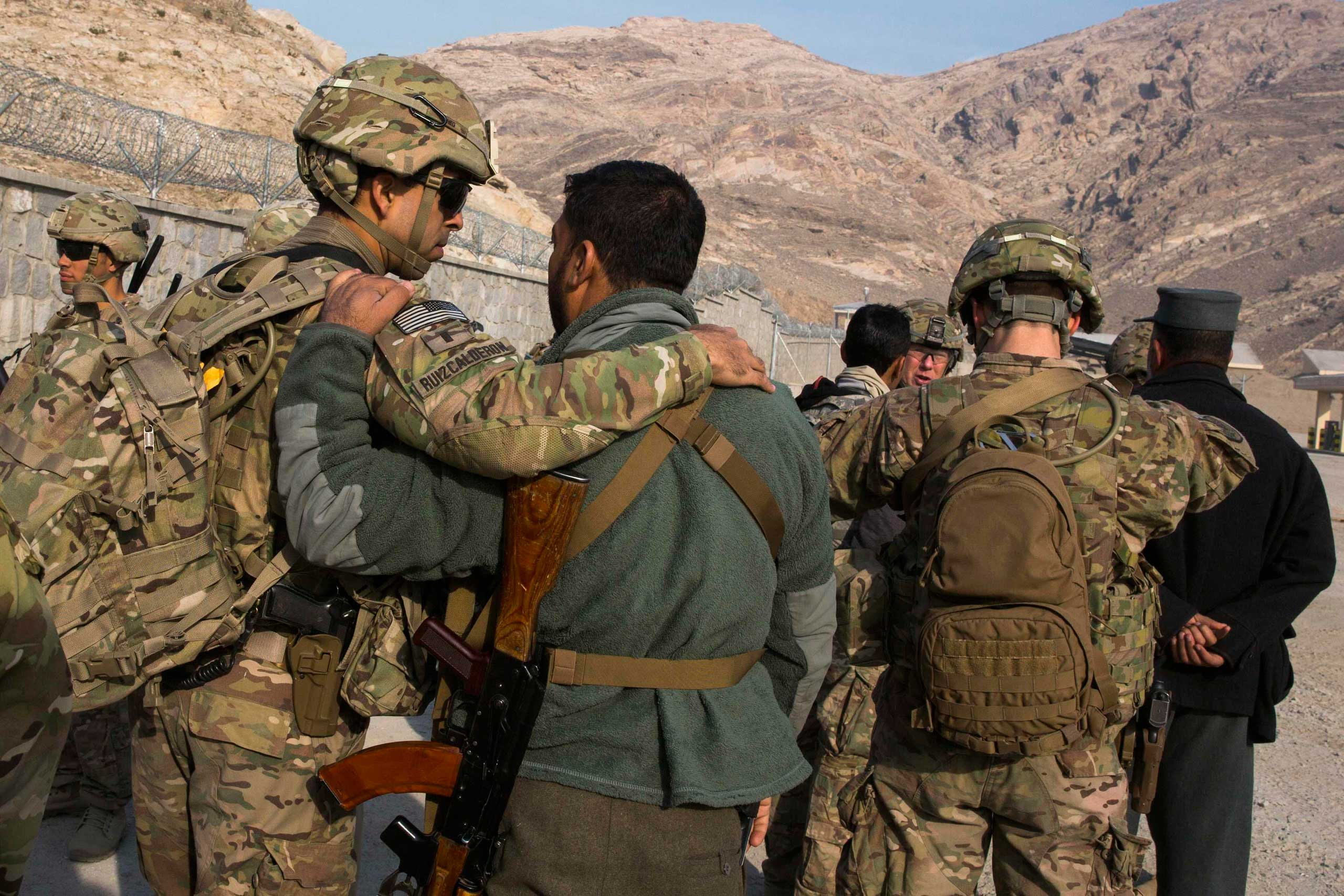 U.S. soldiers from the 3rd Cavalry Regiment greet their Afghan police counterparts during an advising mission near Jalalabad in the Nangarhar province of Afghanistan on Dec. 20, 2014.